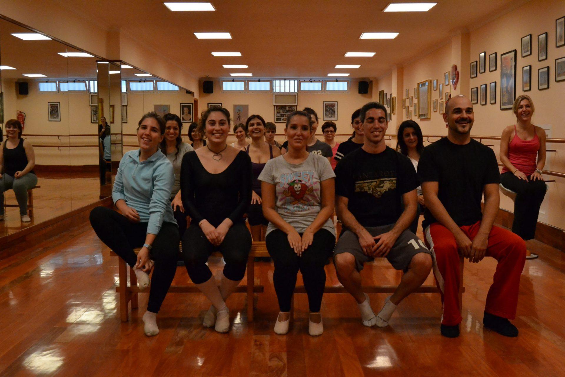 Foto en el Centro de Danza Sandra Santa Cruz de un grupo de bailarines sentados en bancos de madera en la sala de baile... No bailan se preguntarán, sí,  están ensayo del Flashmob en la Escuela Oficial de Idiomas de Las Palmas II.