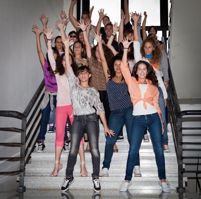 Foto del alumnado del Centro de Danza Sandra Santa Cruz que se levanta y sale del aula para empezar a bailar en las escaleras de la Escuela Oficial de Idiomas.  Un gran grupo de bailarines formando una pirámide sonríen con una mano arriba ¿Cómo acabará su Flashmob...?