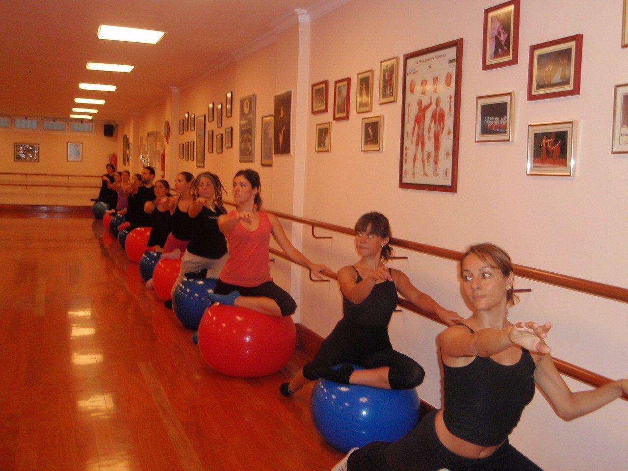 Foto de un gran número de bailarines sobre una pelota de fitball haciendo clase en el Centro de Danza Sandra Santa Cruz