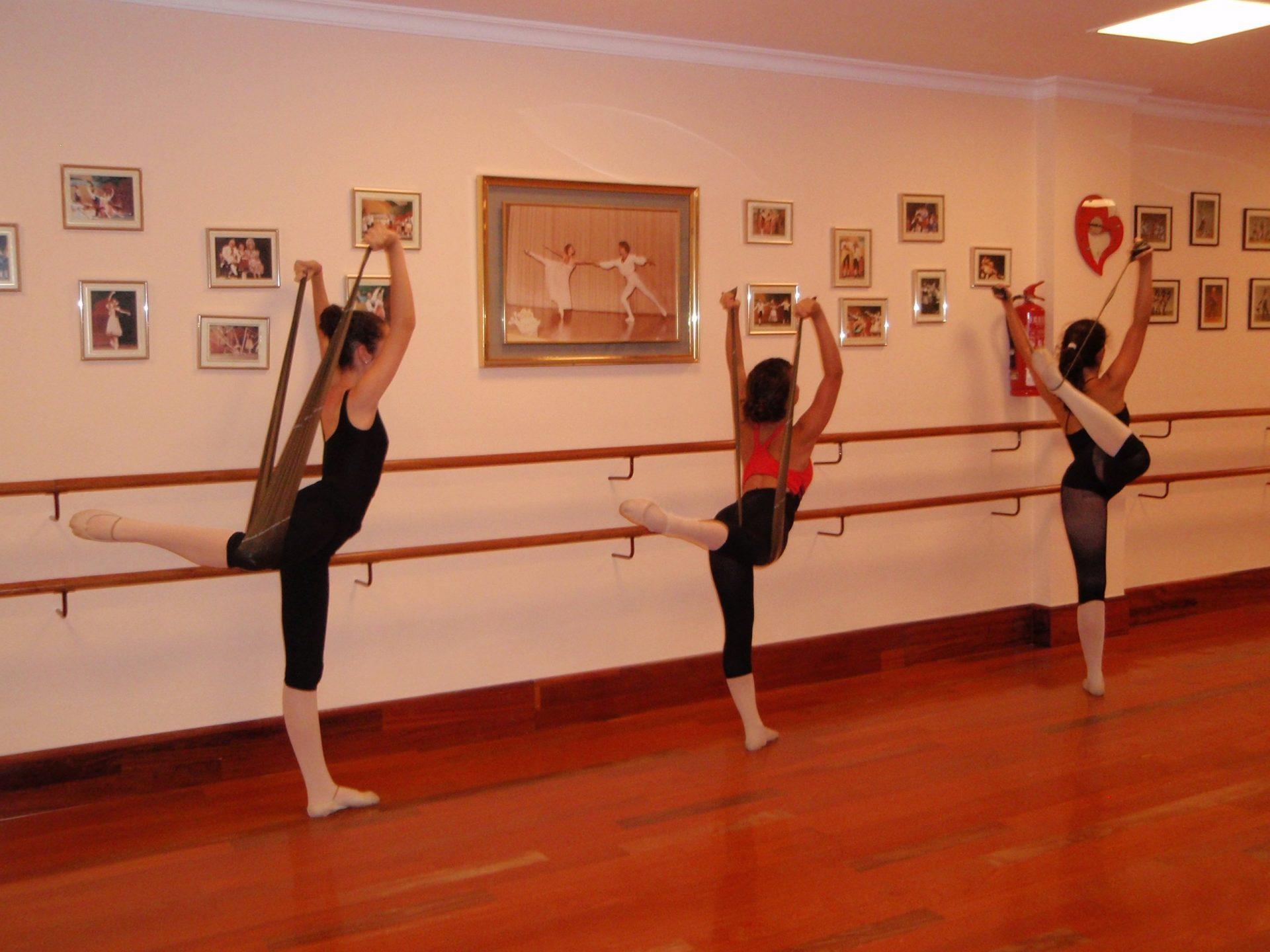 Foto de tres bailarinas en el Centro de Danza Sandra Santa Cruz haciendo un attitude detrás con bandas elásticas.