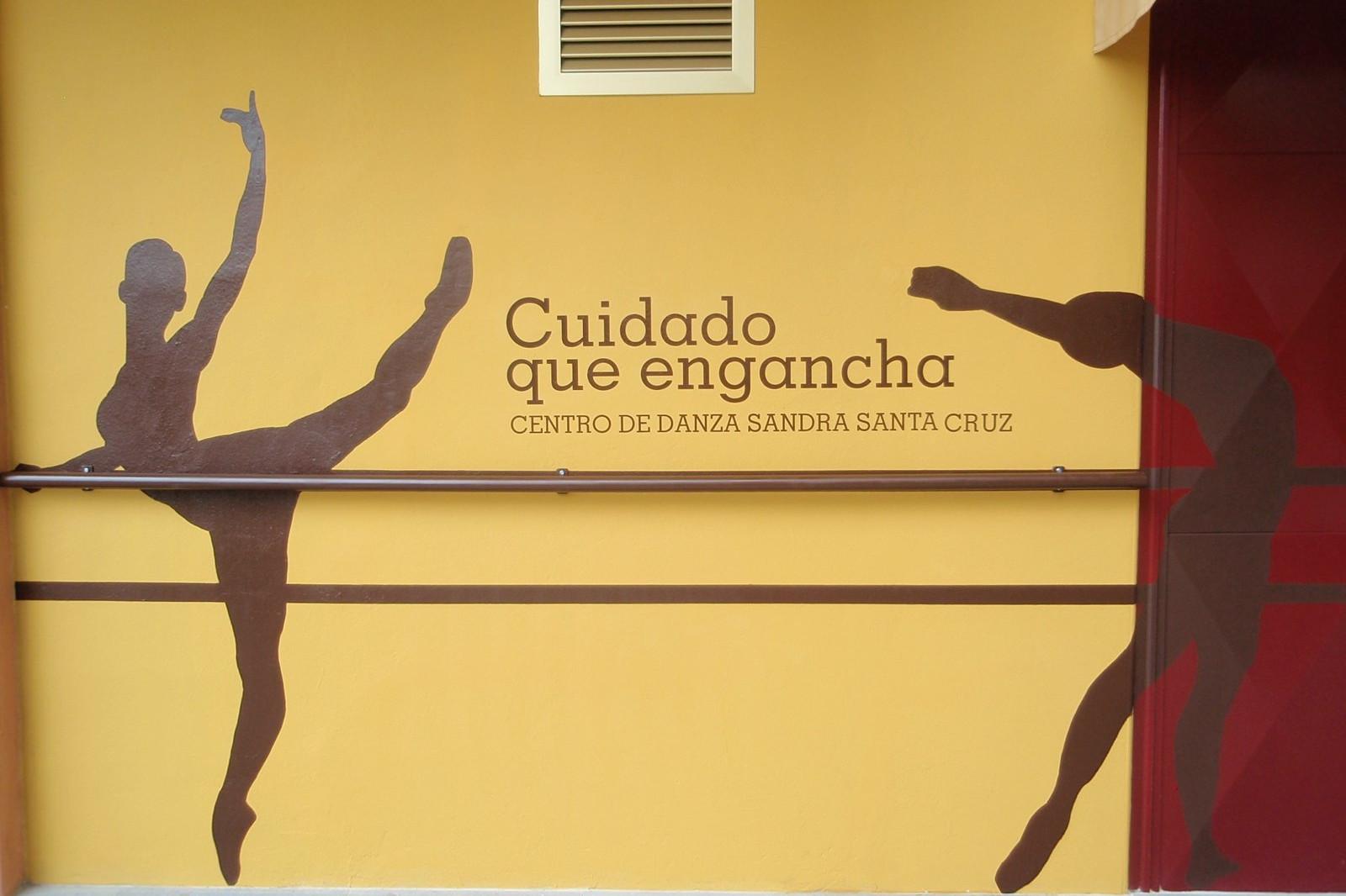 Fachada pintada a tamaño real con la silueta de tres bailarines en diferentes poses y en medio de dos se lee