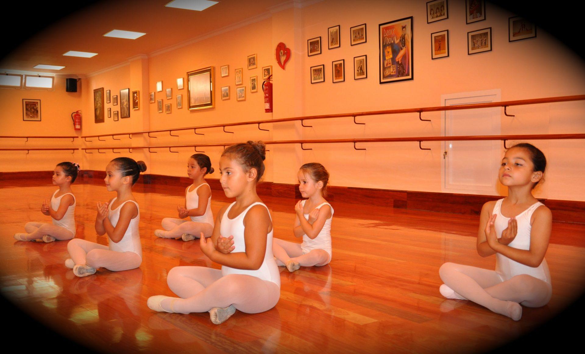 Foto de las alumnas de Predanza I del Centro de Danza Sandra Santa Cruz sentadas en el suelo perfectamente colocadas con los brazos en flor. Estas clases son para alumnoado de 3 a 5 años.