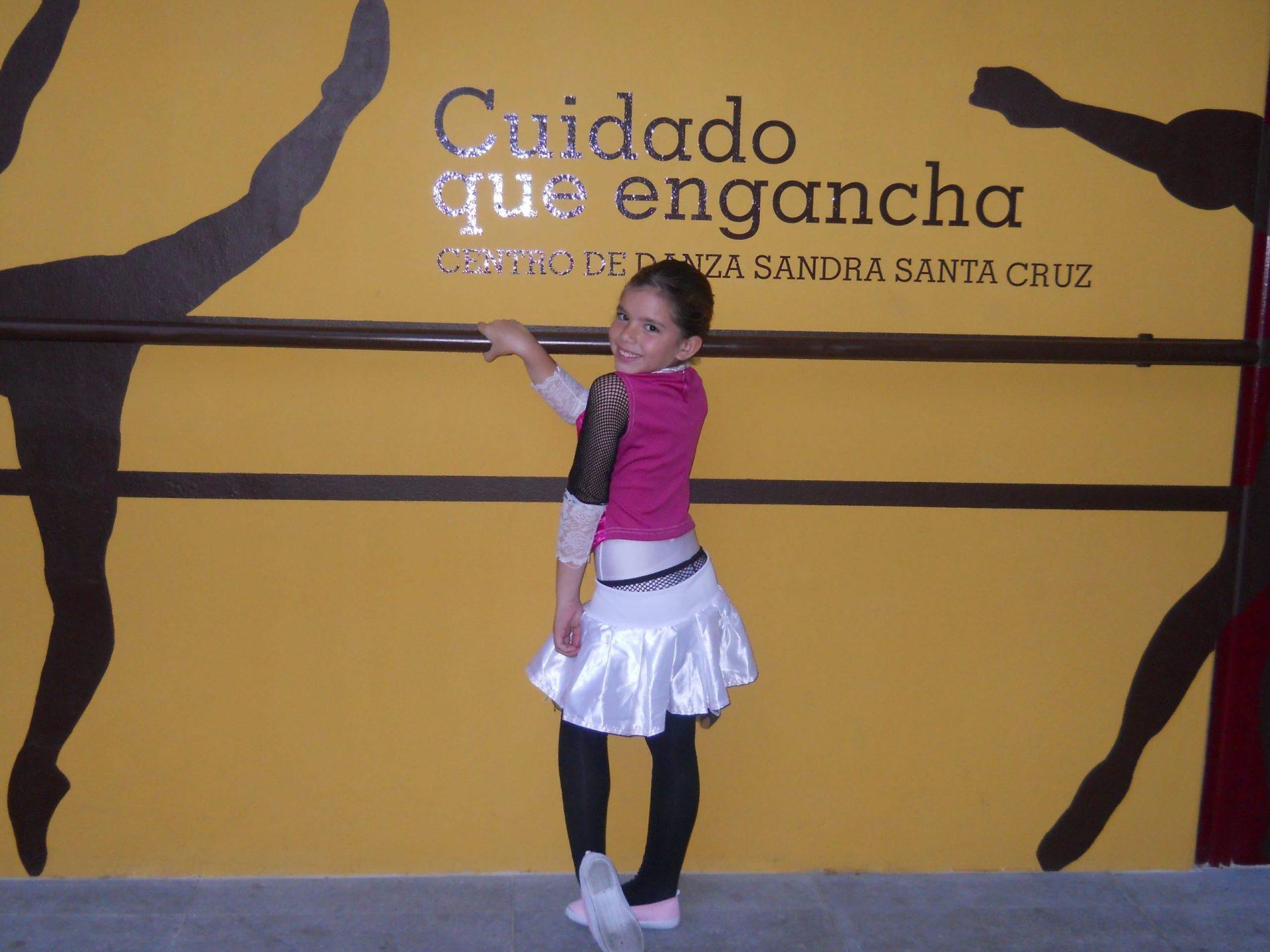 Foto divertida de una alumna de 7 años en la fachada del Centro de Danza Sandra Santa Cruz agarrada a la barra con una pose sexy.