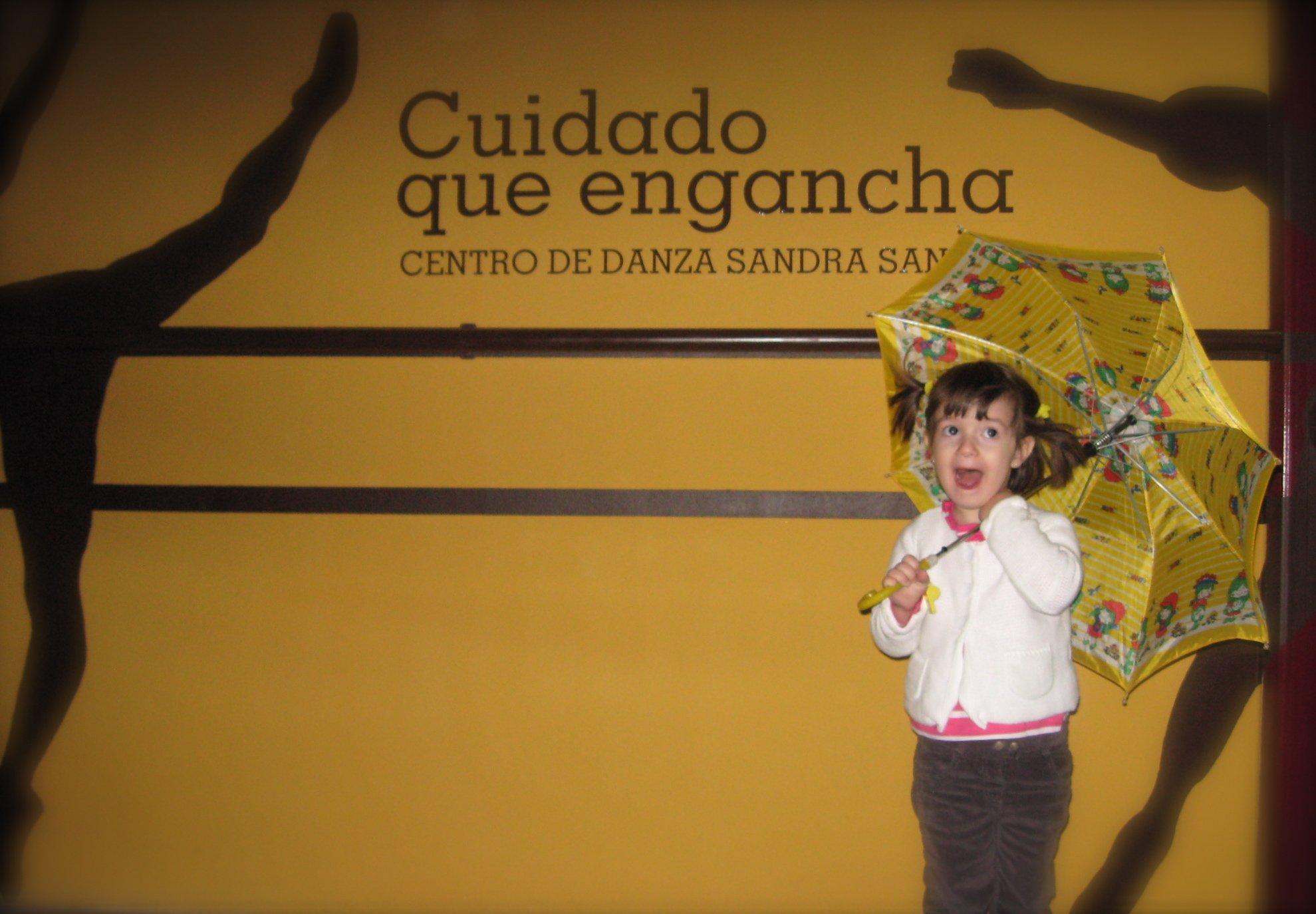 Foto divertida de una alumna de 5 años con dos coletas y la boca abierta en la fachada del Centro de Danza Sandra Santa Cruz agarrada a su paraguas abierto que apoya sobre un hombro.