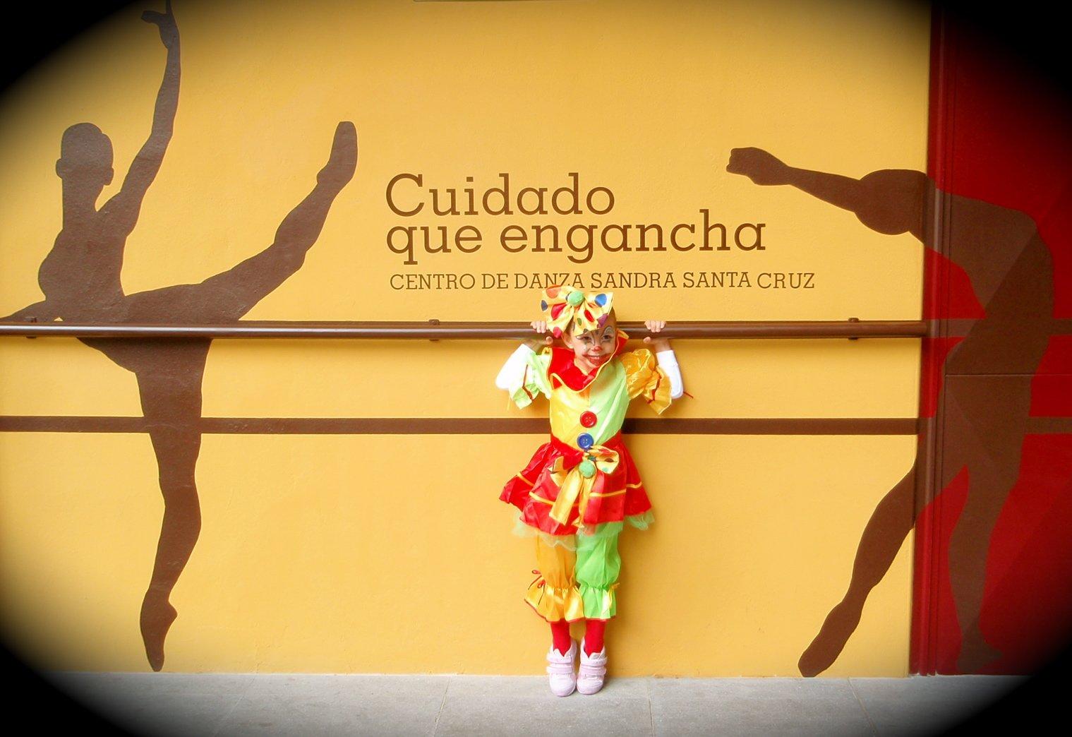 Foto de una alumna de 6 años en la fachada del Centro de Danza Sandra Santa Cruz agarrada a su barra y vestida de payasete.