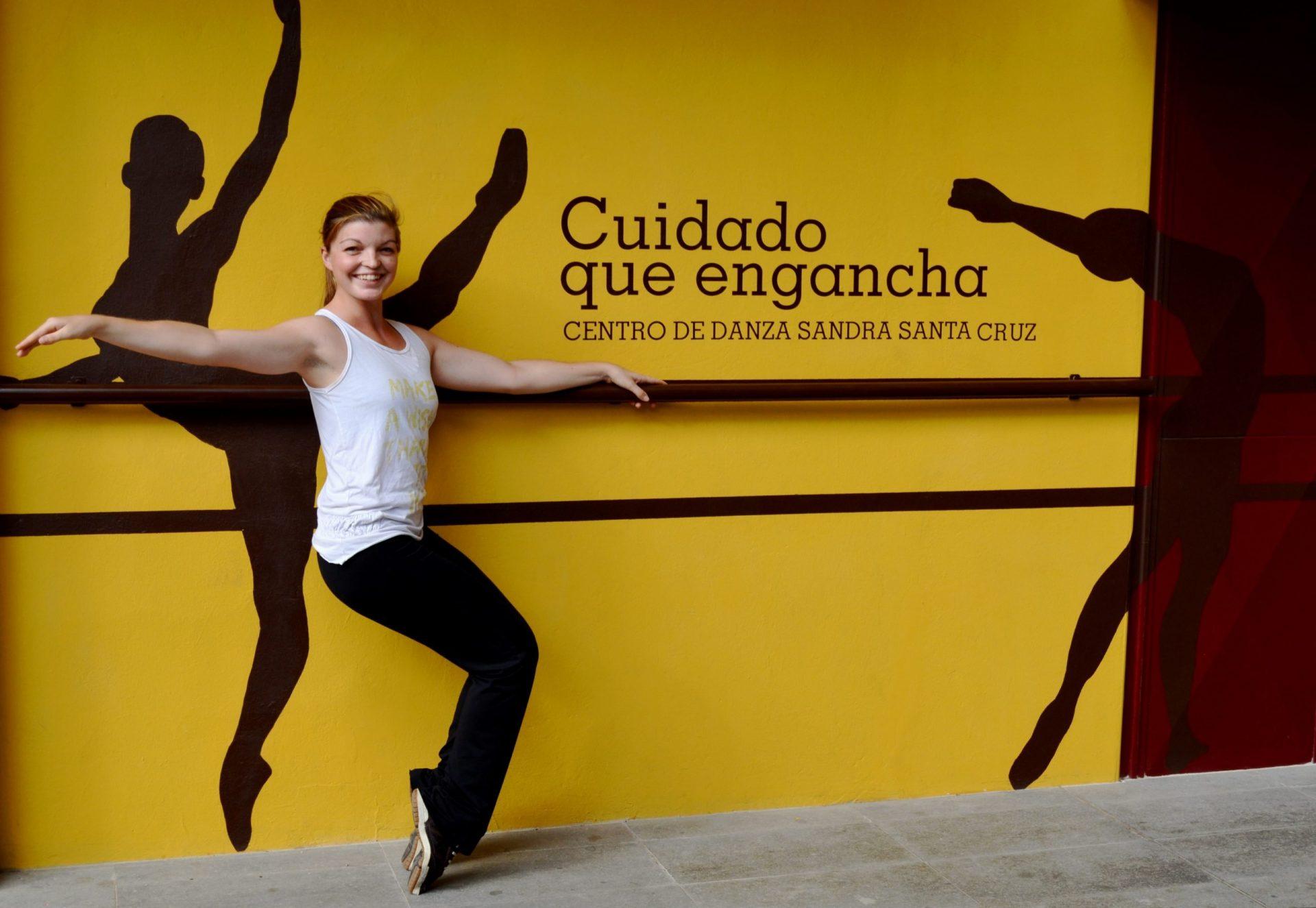 Foto en la fachada del Centro de Danza Sandra Santa Cruz de Alba Montañez agarrada a la barra en una pose de Funky