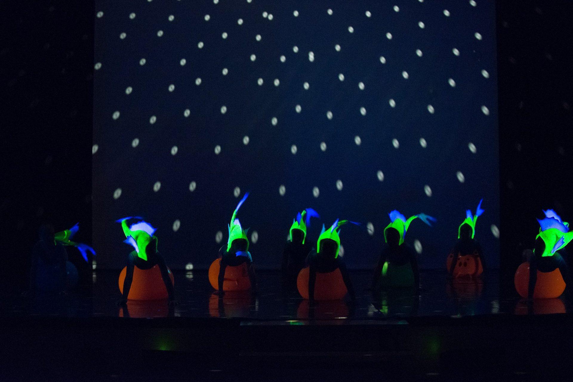 """Foto de una bandada de peces en luz negra del Centro de Danza Sandra Santa Cruz de su Espectáculo """"Con mis mejores deseos"""""""