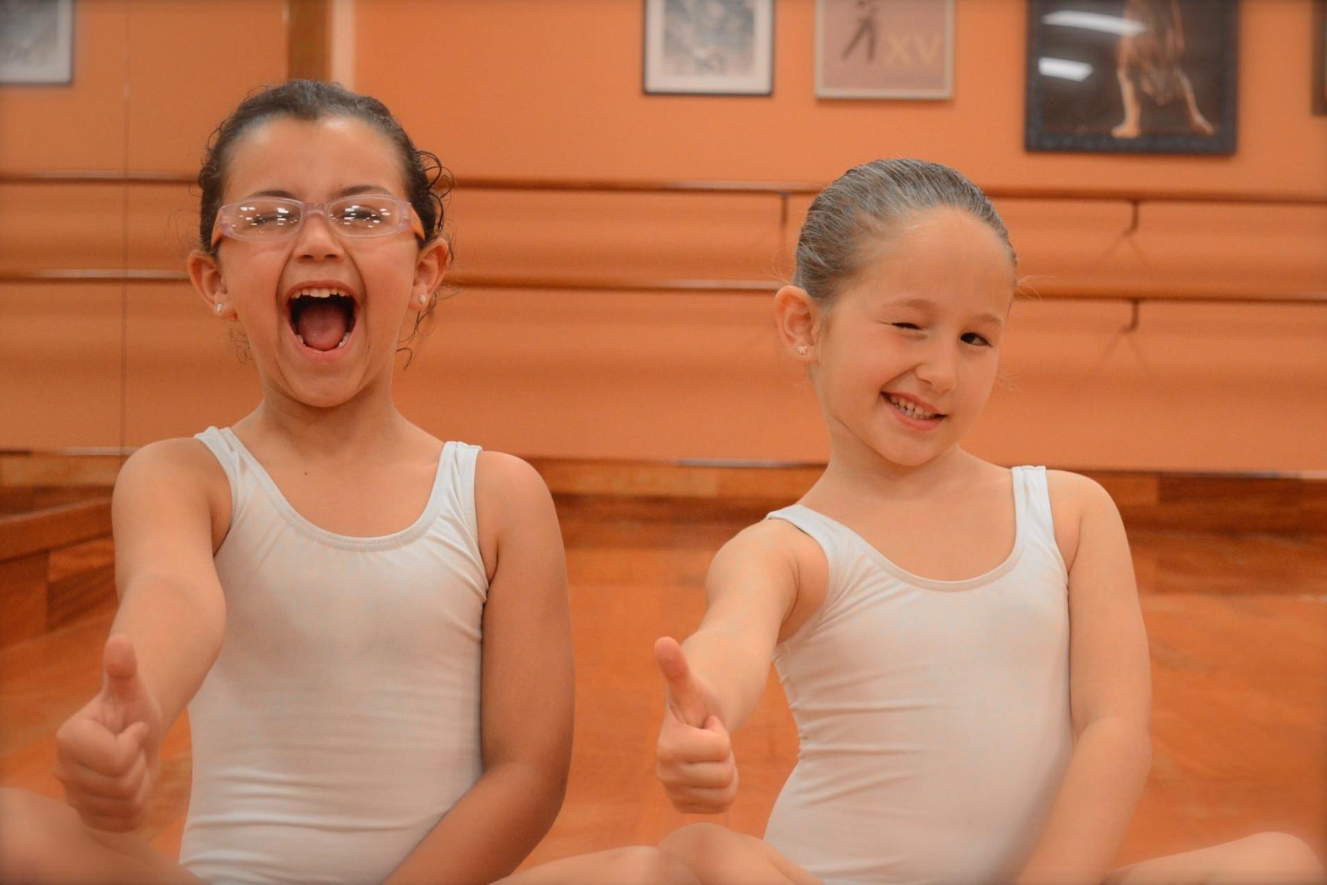Foto de dos alumnas de 5 años del centro de Danza Sandra Santa Cruz sentadas en la Sala de baile qguiñando un ojo y el pulgar de la mano derecha hacia arriba_DSC_0268