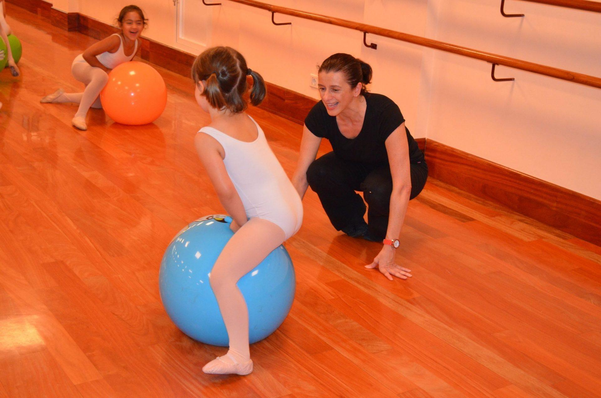Foto en el Centro de Danza Sandra Santa Cruz donde Sandra con una enorme sonrisa da clase a su alumando de Predanza de niños de 3 a 5 años. Dos niñas ríen sentadas sobre unas pelotas de fitball