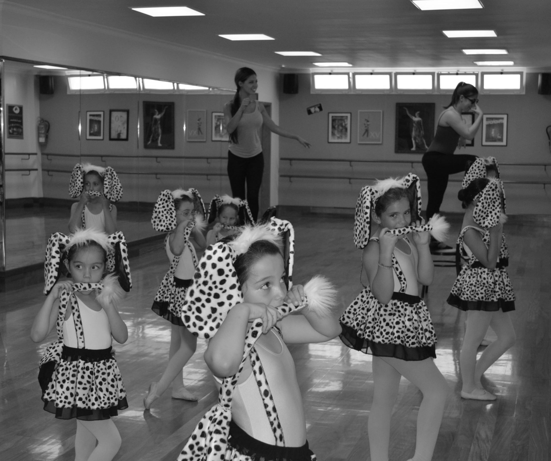 Foto de un grupo de alumnas de Predanza II de 6 años, vestidas de dámatas con una diadema con enormes orejitas y que, con una pose sexy se muerden el rabito que sale de sus faldas. Están en un ensayo del Centro de Danza Sandra Santa Cruz para los espectáculos para diciembre.