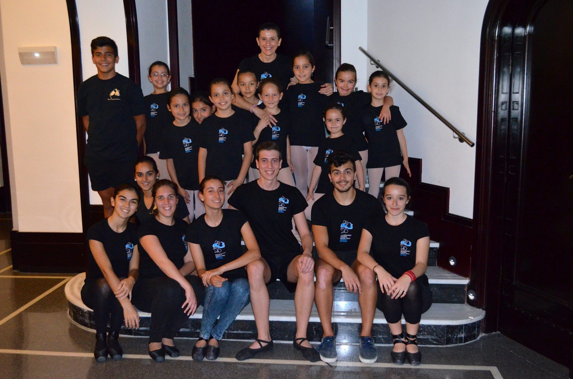Foto de un grupo de baialrines del Centro de Danza Sandra Santa Cruz sentados en la escalera del Teatro Guiniguada para celebrar  el Día Mundial de la Danza