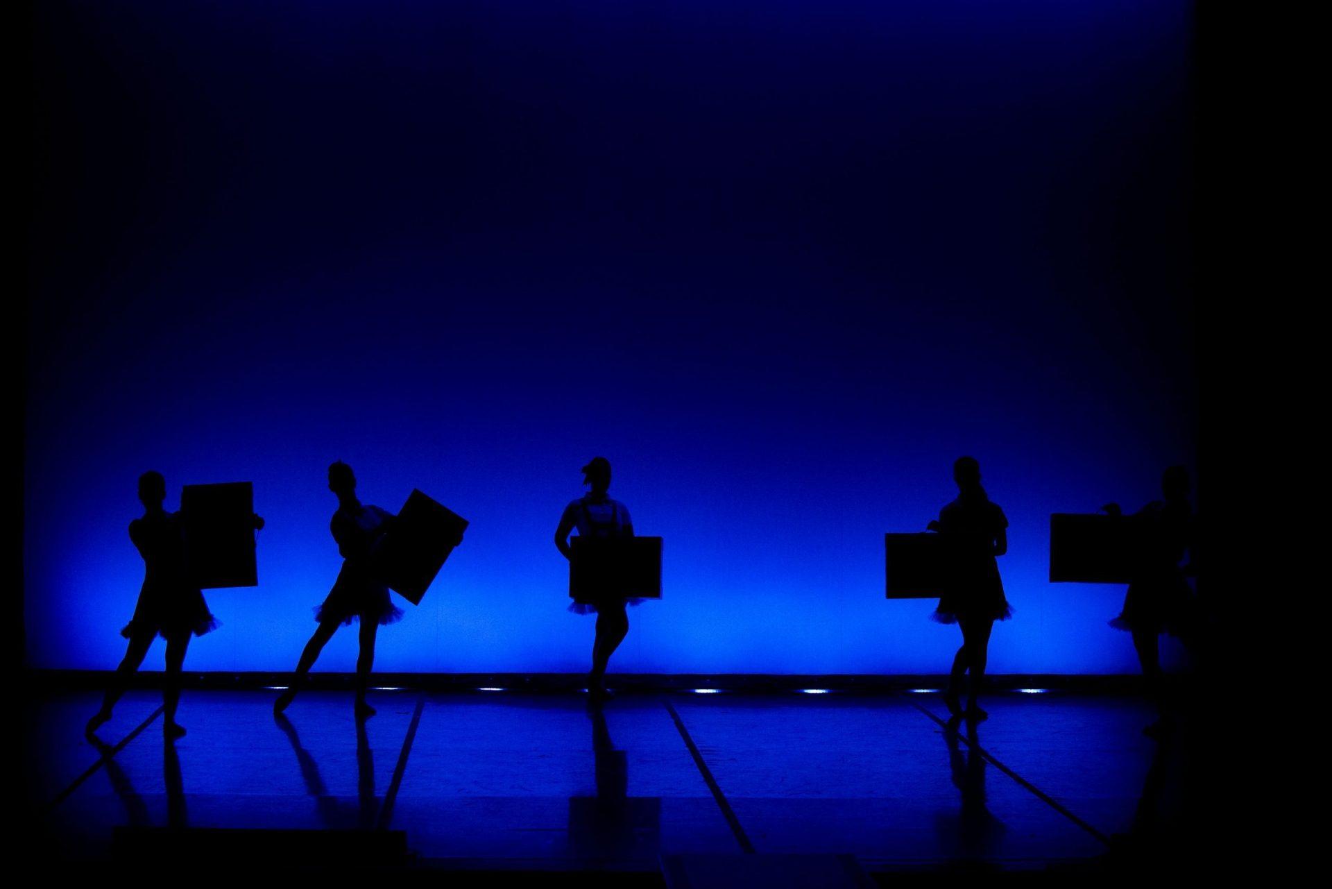 Foto de la silueta de un grupo de bailarinas del Centro de Danza Sandra Santa Cruz en su 25 Aniversario. En distintas poses y con una maletas cada una, simboliza el paso de los años.