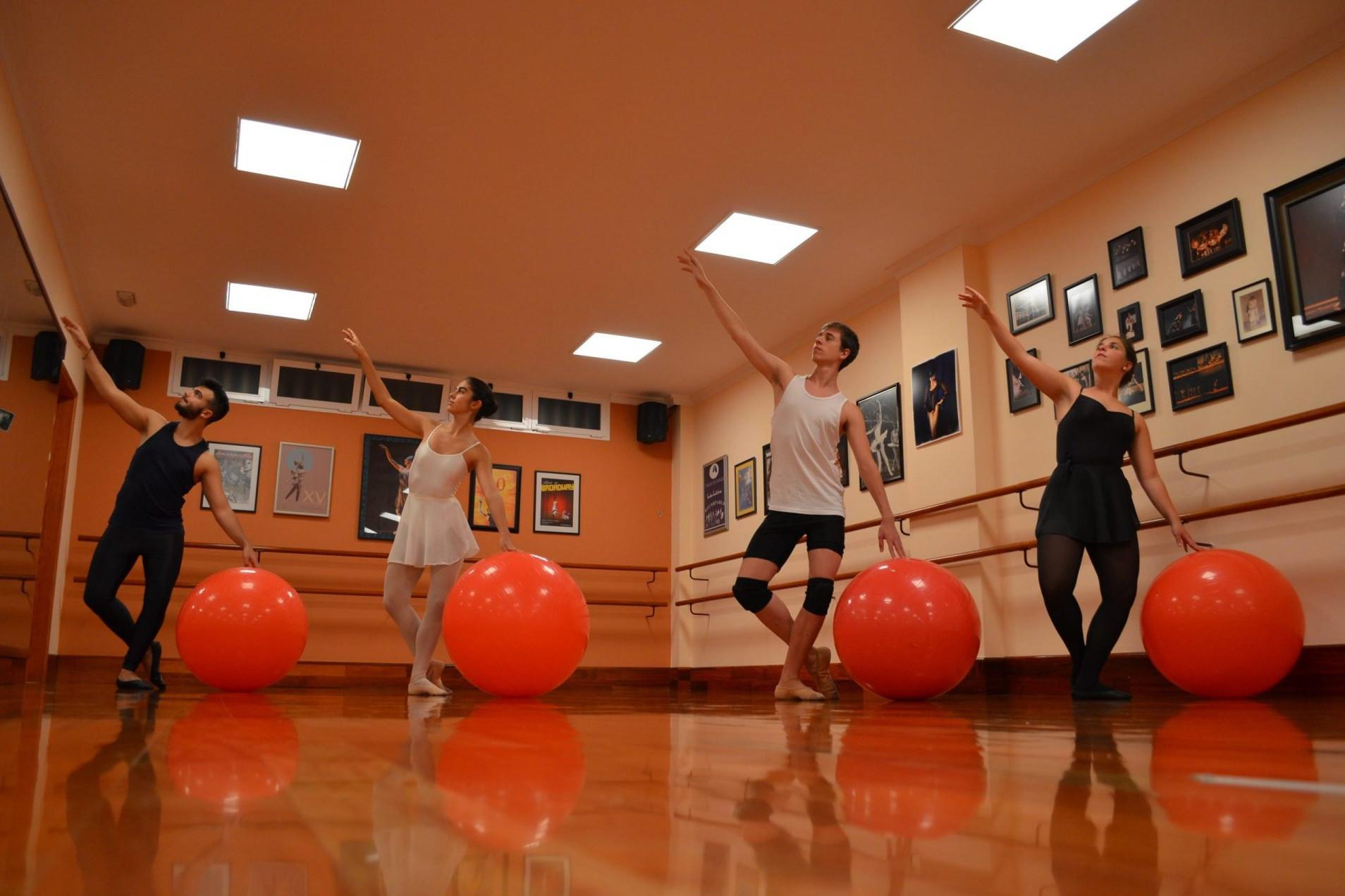 Foto en el Centro de Danza Sandra Santa Cruz de un grupo de bailarines con una pelota grande durante una clase de Stretching con fit-ball y bandas elásticas para tener mejor forma física.