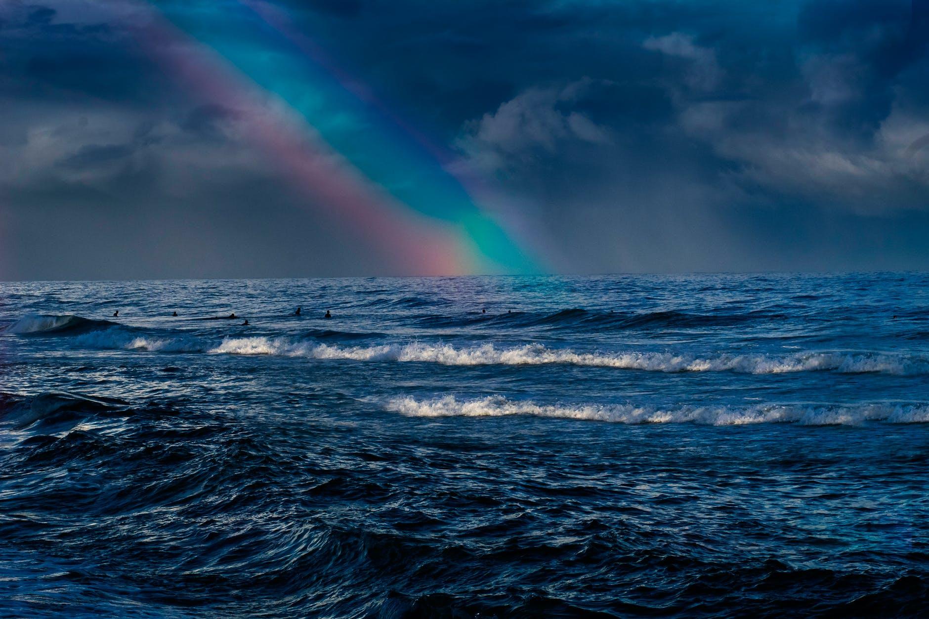ocean waves under rainbow and cloudy sky