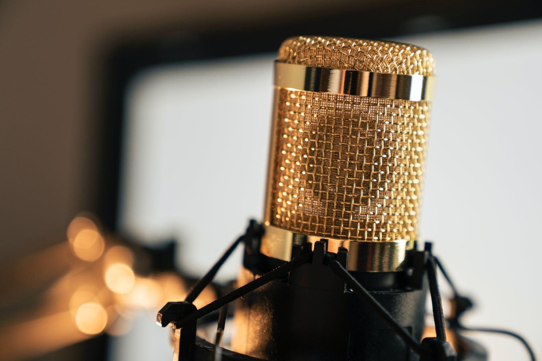 Micrófono de mano dorado sobre un pie de base negro utilizado de cabecera por Sandar Santa Cruz para ofrecer que escuchen en primicia ¡¡Yuju Don Canino!! una de las canciones que se han creado paar el Musical