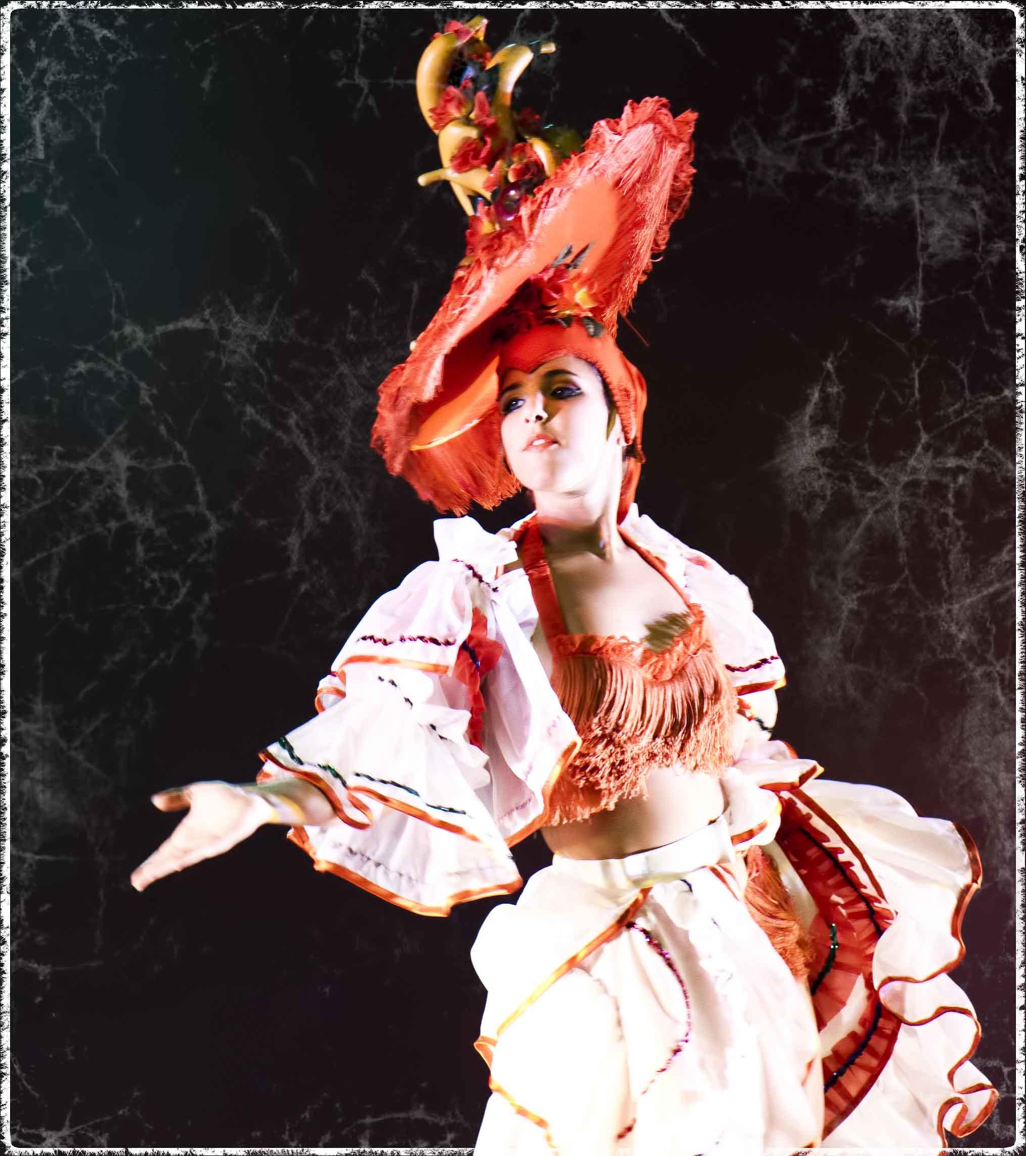 """Foto de una bailarina de la Compañía de Danza Sandra Santa Cruz bailando de rumbera """"Fashion Dance Show"""" con un gigantesco gorro con fleco alrededor y lleno de frutas tropicales."""