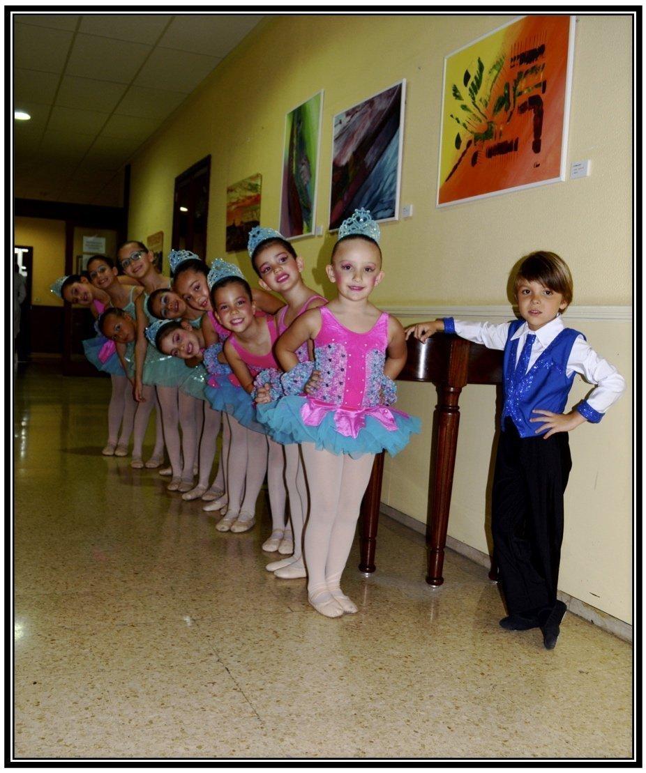 Foto de un grupo de bailarinas de 6 años en fila y delante un bailarín de su mima edad con una mano e la cintura en pose chula durante una actuación delCentro de Danza Sandra Santa Cruz
