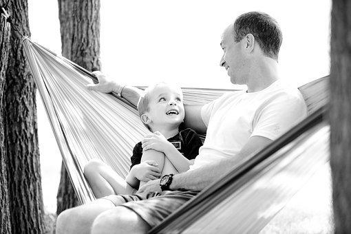 Foto de un padre sentado en una hamaca con su hijo pequeño