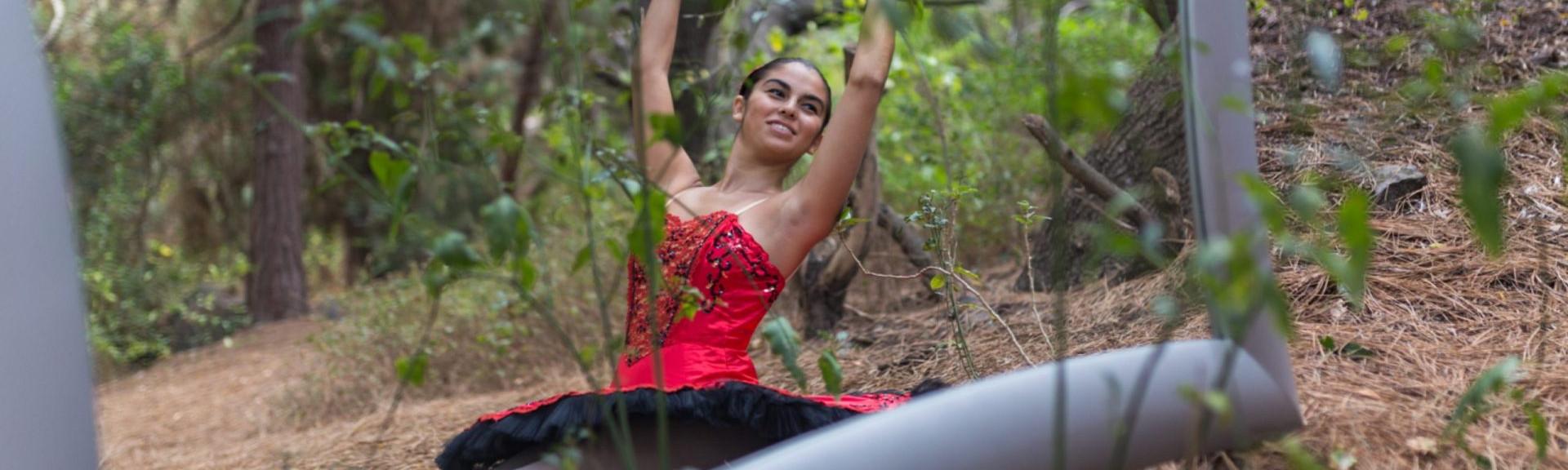 Foto de una bailarina del Centro de Danza Sandra Santa Cruz en el campo sentada con los pies estirados y haciendo un cambré ante un gran espejo. Tiene zapatillas de puntas y un espectacular tutú de plato en color rojo con adornos en negro, para explicar que el trabajo en el Centro es: Muchomasquedanza