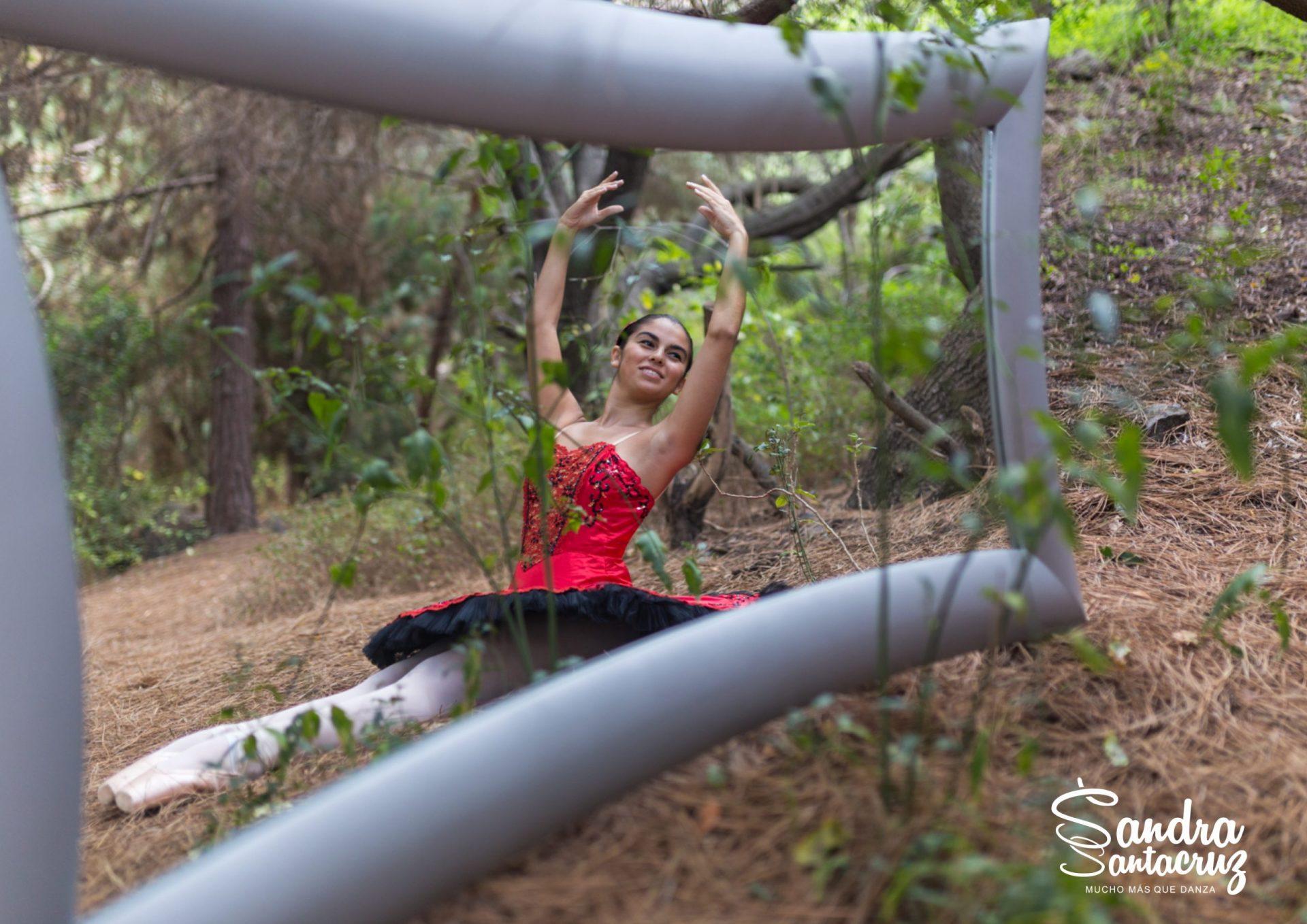 Foto de una bailarina del Centro de Danza Sandra Santa Cruz en el campo sentada con los pies estirados y haciendo un cambré ante un gran espejo. Tiene zapatillas de puntas y un espectacular tutú de plato en color rojo con adornos en negro, para explicar que el trabajo en el Centro es: Muchomasquedanza. Fotografía Ethel Bartrán.