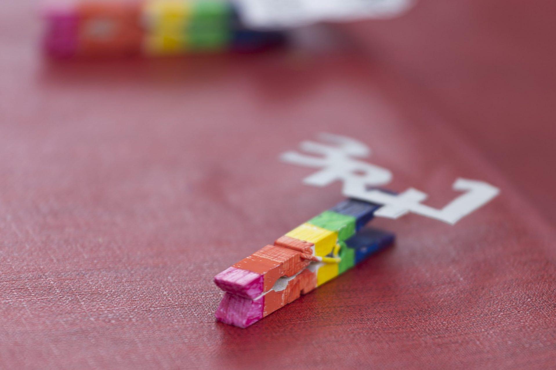Foto de una traba de la ropa pintada con los colores del arcoíris y lleva pegado en material recicado con brick de leche la frase 3R+1. Taller de reutilización de Sandra Santa Cruz.