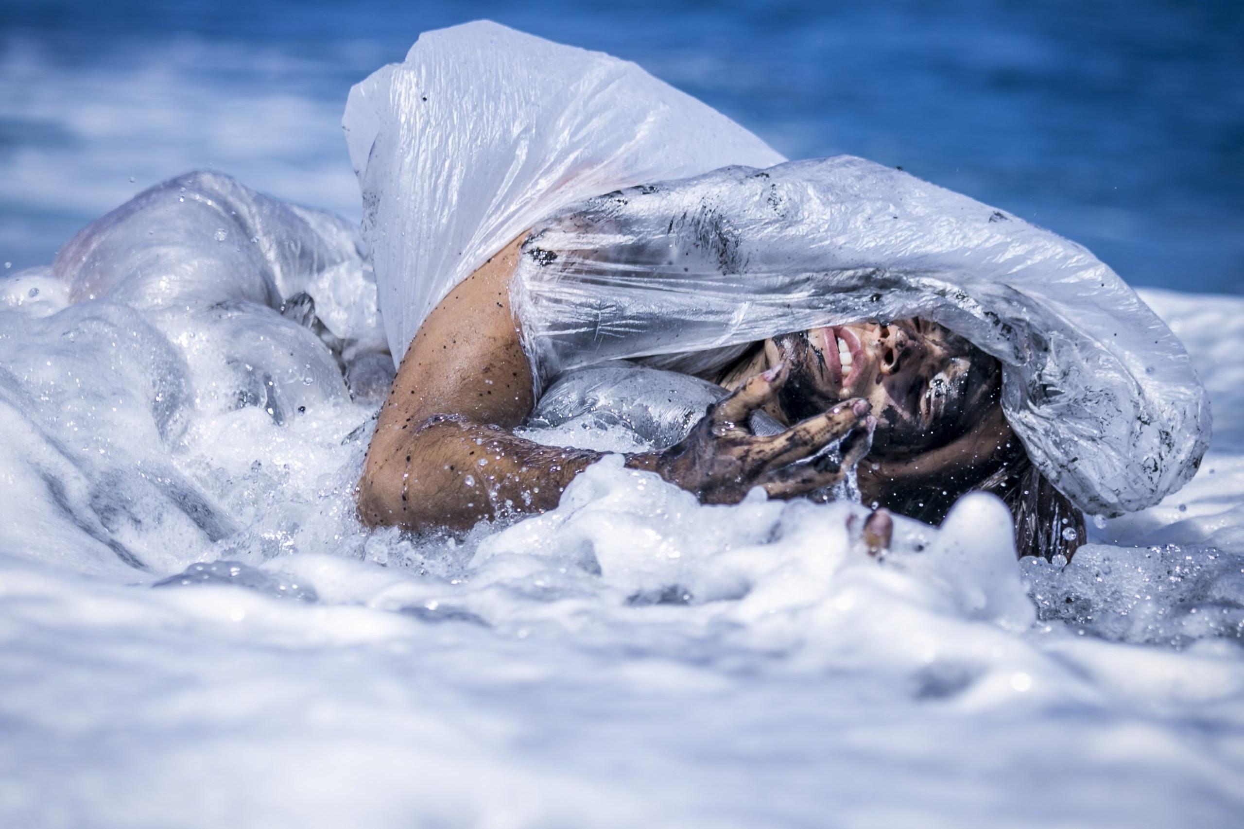 Una modelo está enredada en plástico y alquitrán mientras es vapuleada por las olas del mar. Fotografía de