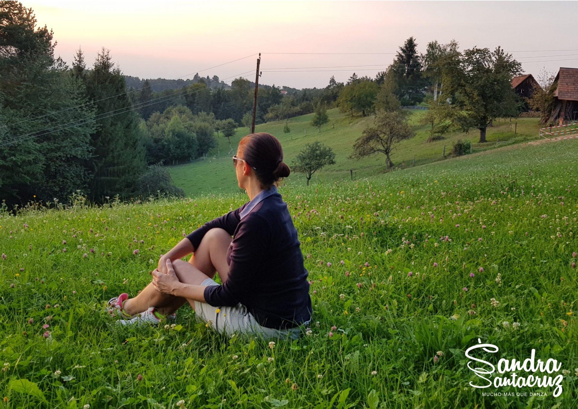 Sandra Santa Cruz sentada en un precioso prado mira las montañas de Austria y piensa en el retorno a su Centro.
