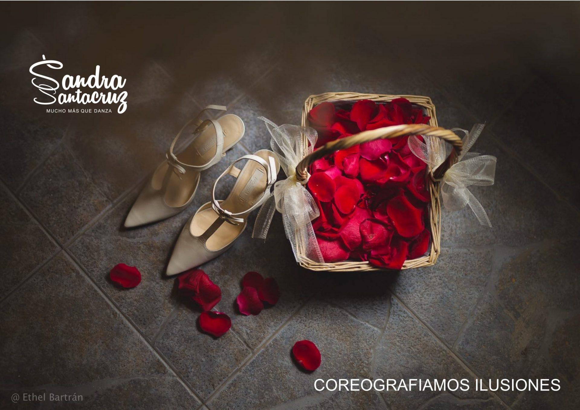 Foto de unos zapatos de boda de tacón al lado de una cesta de mimbre con pétalos de rosas rojas para anunciar la clase DANCE TOGETHER del Centro de Danza Sandra Santa Cruz. Fotografía de Ethel Bartán.