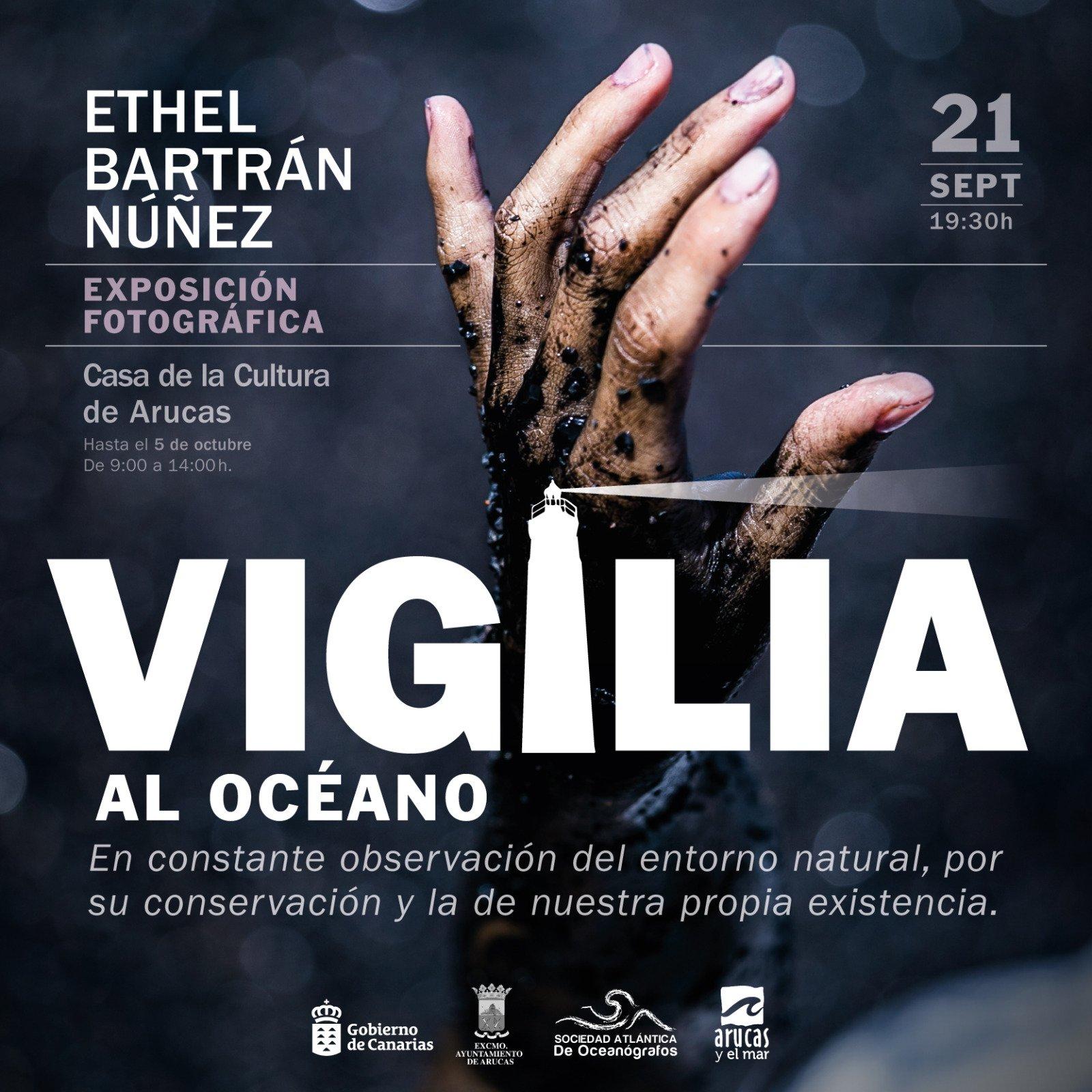 """Cartel de la exposición fotográfica """"Vigilia al Océano"""" de Ethel Bartrán donde una mano llena de alquitrán sube hacai arriba buscando tu ayuda."""