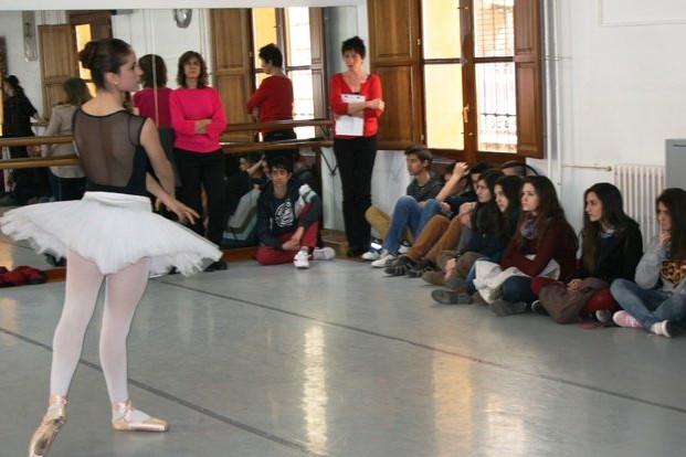 Foto de una baialrina con un tutú en una sala de baile y público sentado en el suelo. Jornada de puertas abiertas del Conservatorio de Alicante