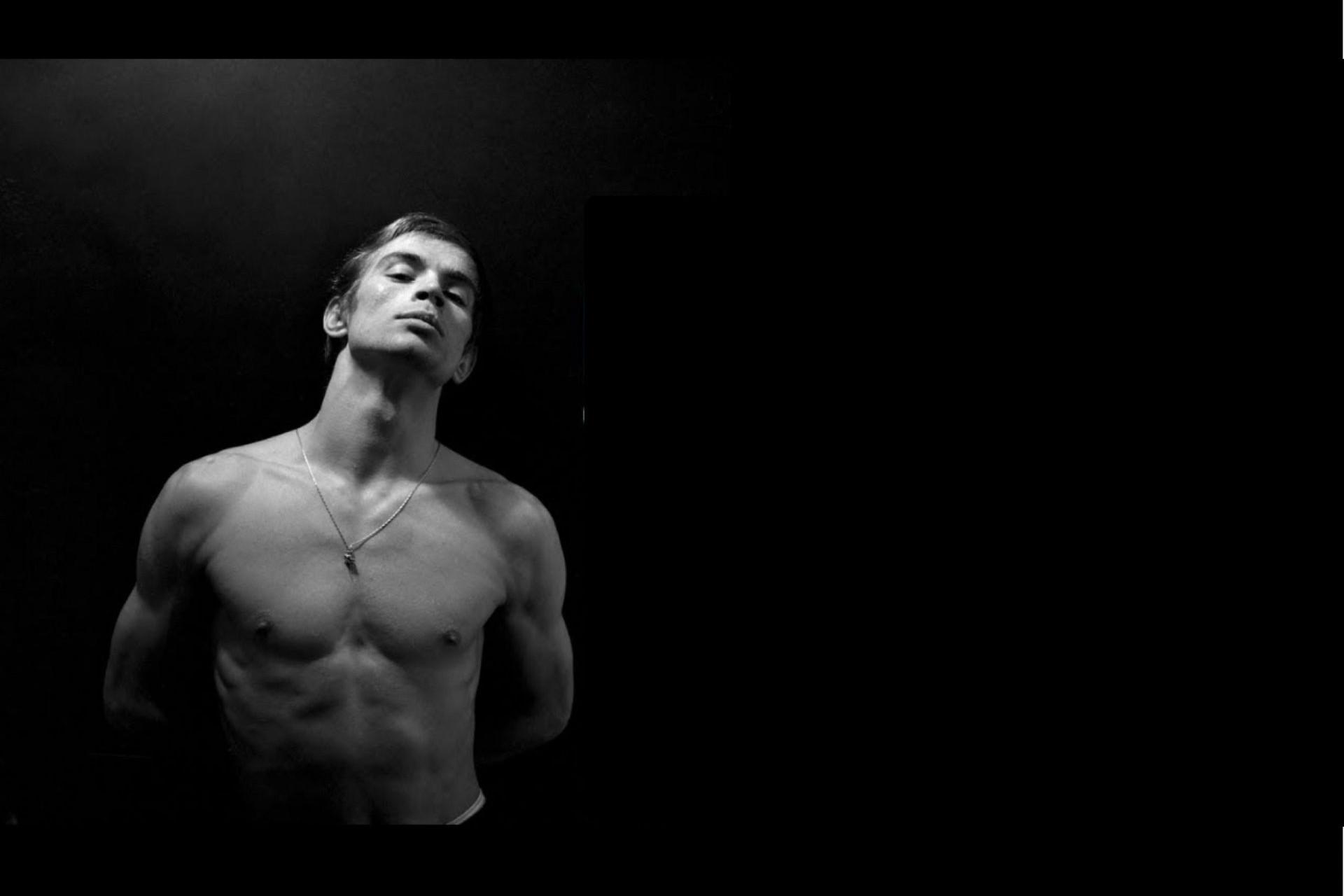Foto de Rudolf Nureyev_El bailarín a torso descubierto con las manos detrás de la espalda.