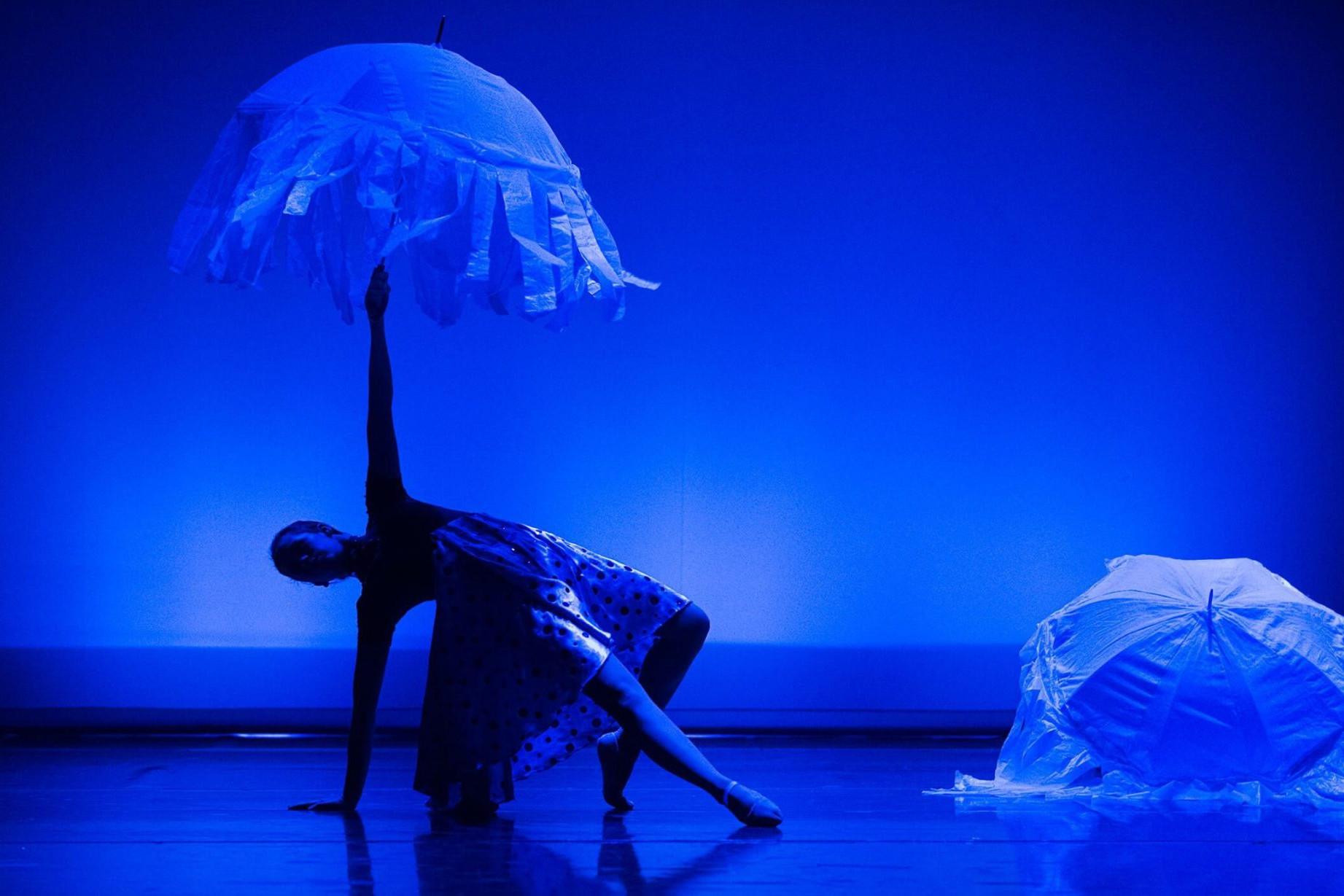 Foto de dos bailarinas del Centro de Danza Sandra Santa Cruz iluminadas en azul mar bailando con paraguas blancos decorados como medusas. Coreografía de Sandra Santa Cruz en su espectáculo: Con mis mejores deseos.