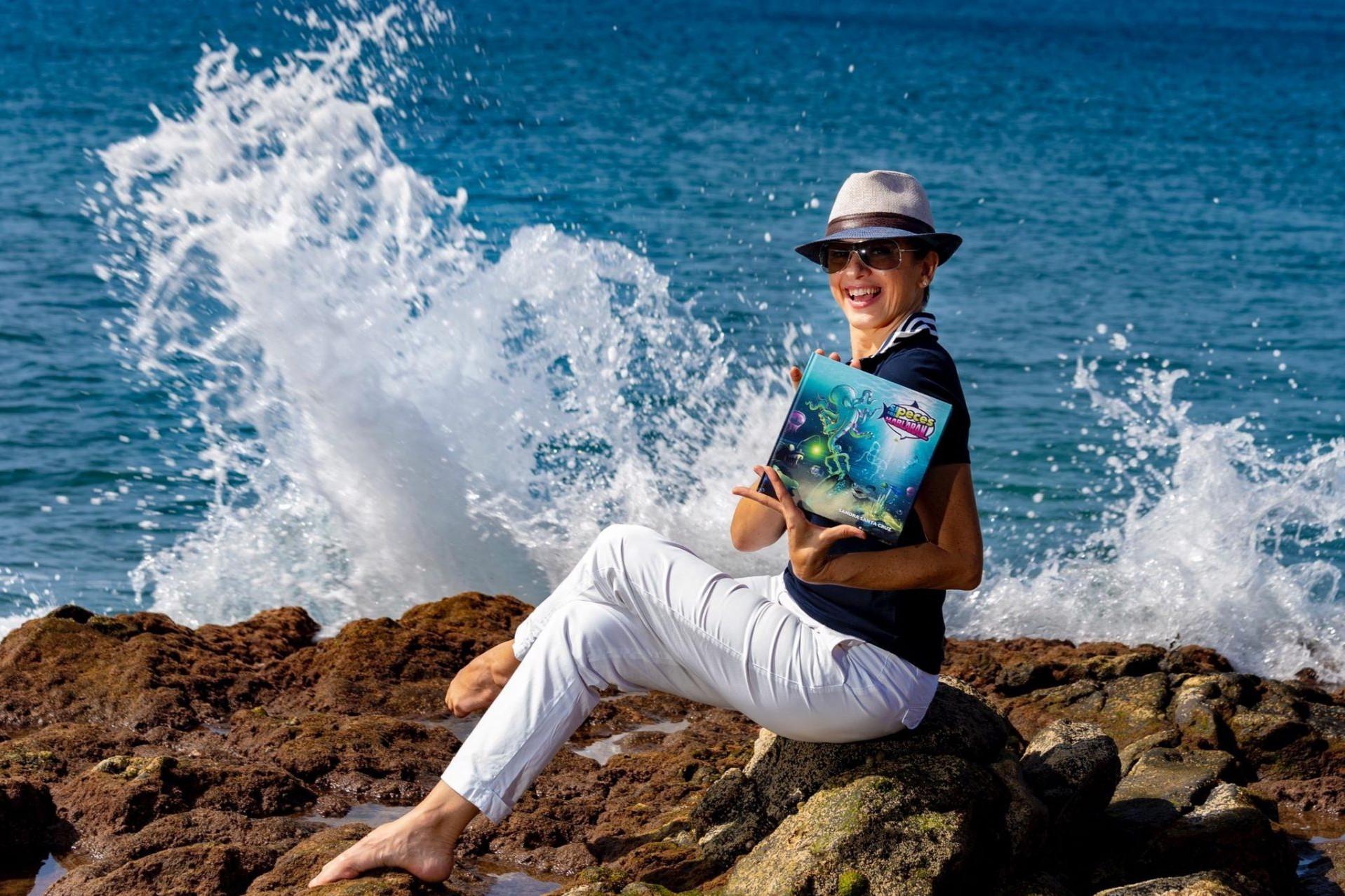 Foto de Sandra Santa Cruz sentada en unas rocas con su cuento Si los peces hablaran... en las manos, con el mar de fondo y unas olas rompiendo detrás de ella. Su cuetno quiere ayudar a proteger el mundo marino y frenar la contaminación. Entrevista en la revista Enjoy