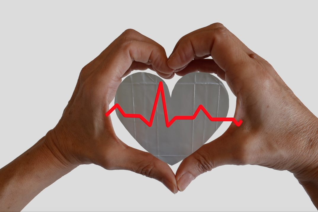 Foto de las manos de Sandra Santa Cruz abrazando a un corazón que en el centro tiene los latidos del corazón. Taller de reutilización