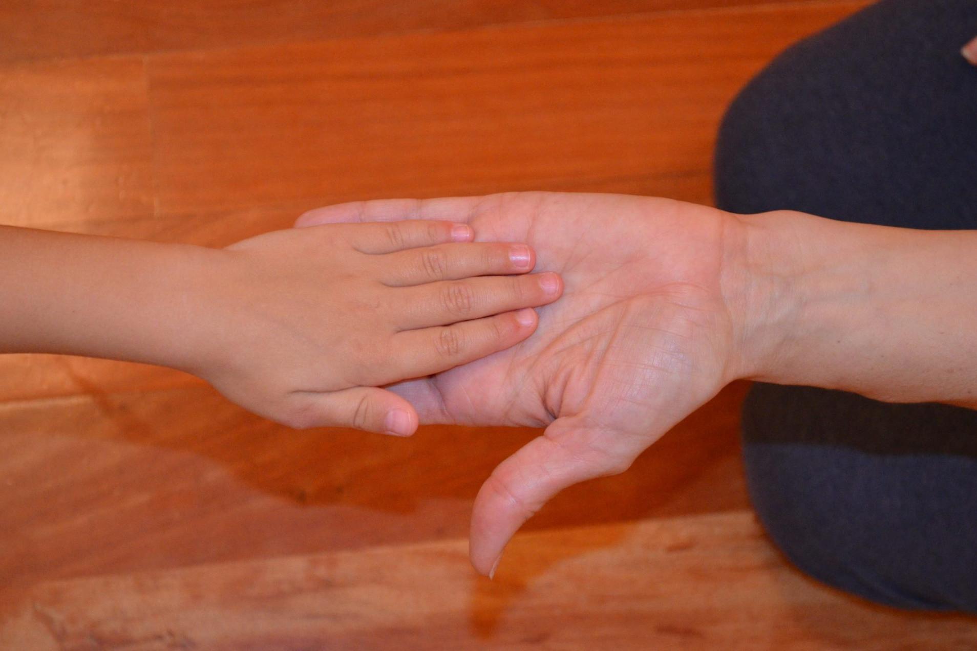 Foto de la mano de Sandra Santa Cruz la salud es lo que prima. Foto de una mano adulta sujetando la mano de una niña