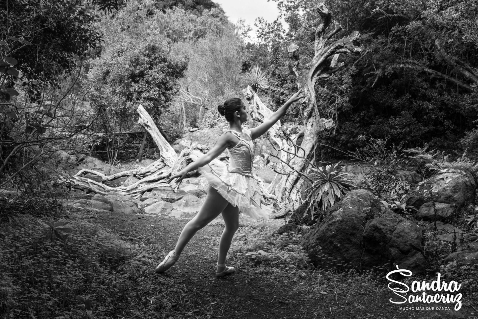 Foto de una bailarina del Centro de Danza Sandra Santa Cruz con un tutú blanco haciendo un arabés en alonyé en el campo.