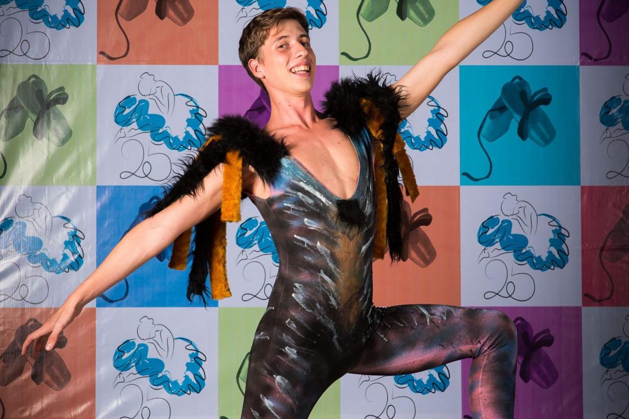 Foto de un bailarín vestido de gato posando de rodillas en 4ª y los brazos en alonyé en el photocall del 25 Aniversario delCentro de Danza Sandra Santa Cruz