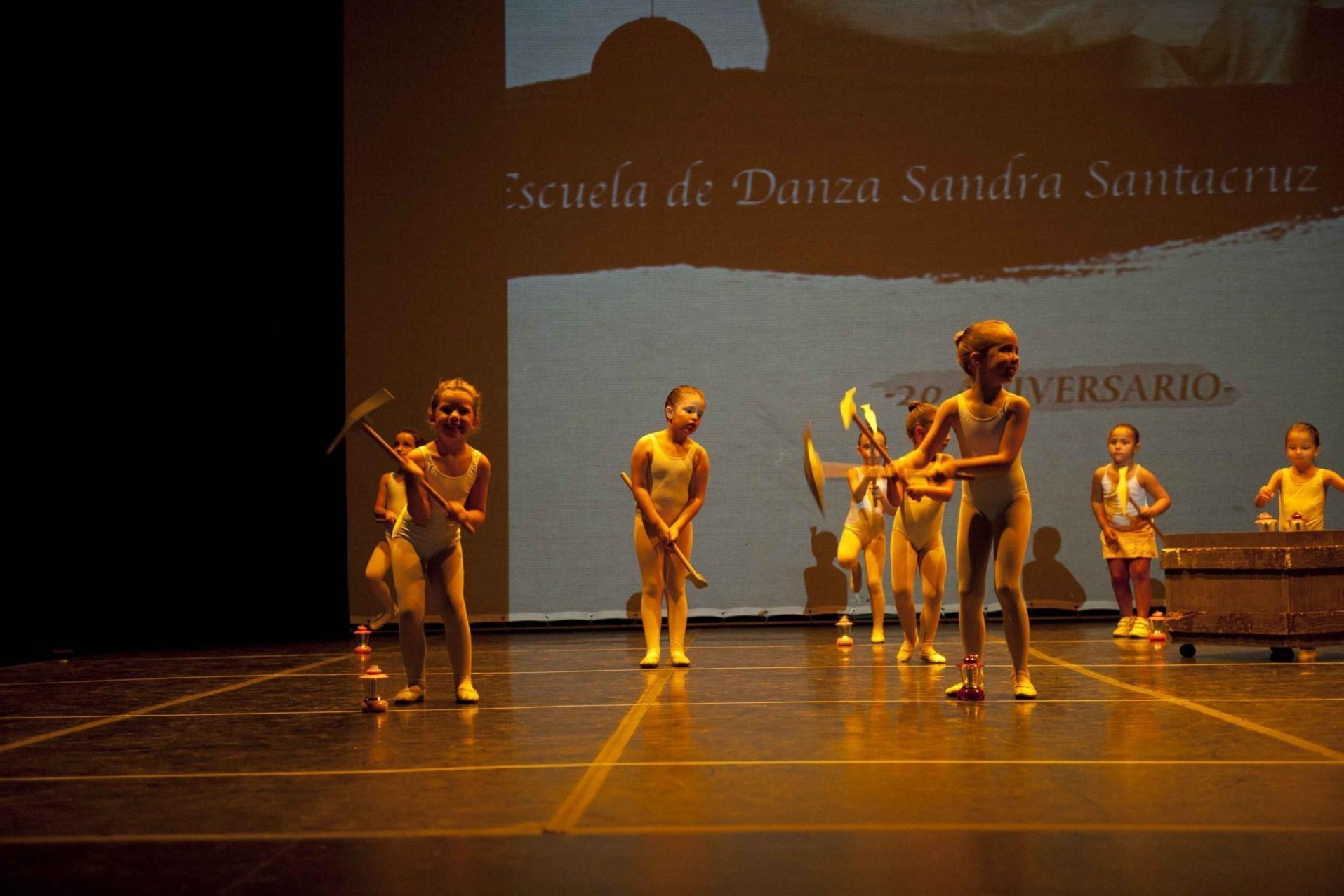 Foto del 20 Aniversario del Centro de Danza Sandra Santa Cruz donde las alumans de Predanza están en el escenario con unos picos y un carrito para bailar Blancanieves
