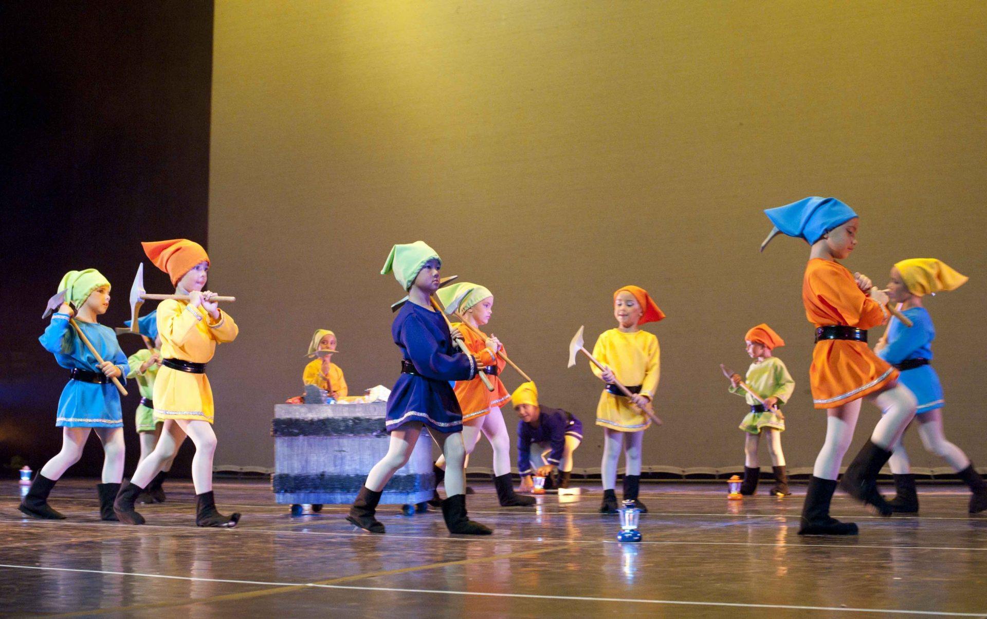 Un grupo de enanitas con pico al hombro caminan por el escenario para llevar los diamantes a la carretilla que tienen tras de sí. Son las alumnas de Predanza del Centro de danza Sandra Santa Cruz