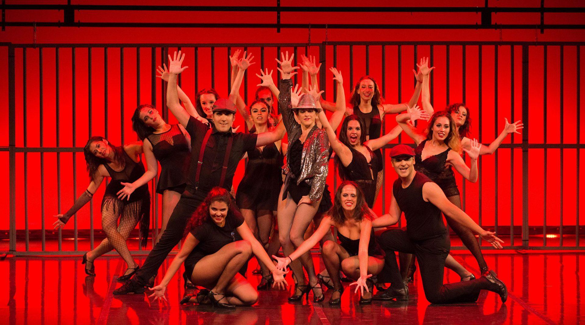 Foto del Centro de Danza Sandra Santa Cruz en su 25 Aniversario donde un grupo numeroso de bailarines delante de unas rejas iluminadas en rojo baila Cell Block Tango del Musical Chicago