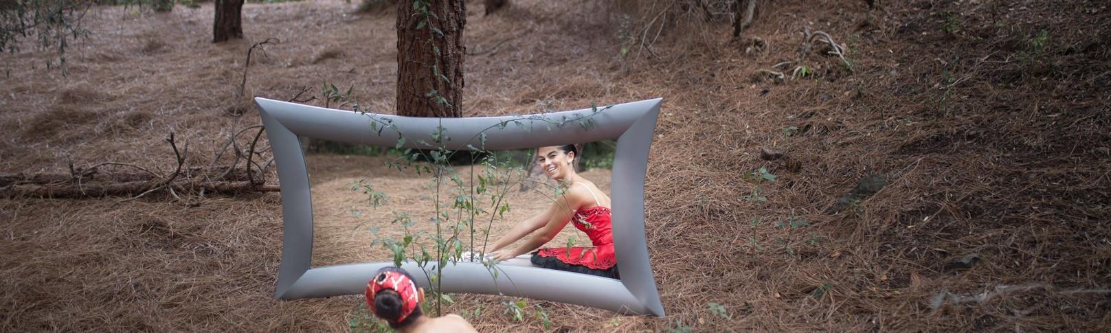 Foto de una bailarina del Centro de Danza Sandra Santa Cruz en el campo sentada con los pies estirados y las manos apoyadas en los pies mirándose sonriéndo ante un gran espejo. Tiene zapatillas de puntas y un espectacular tutú de plato en color rojo con adornos en negro, para explicar que el trabajo en el Centro es: Muchomasquedanza