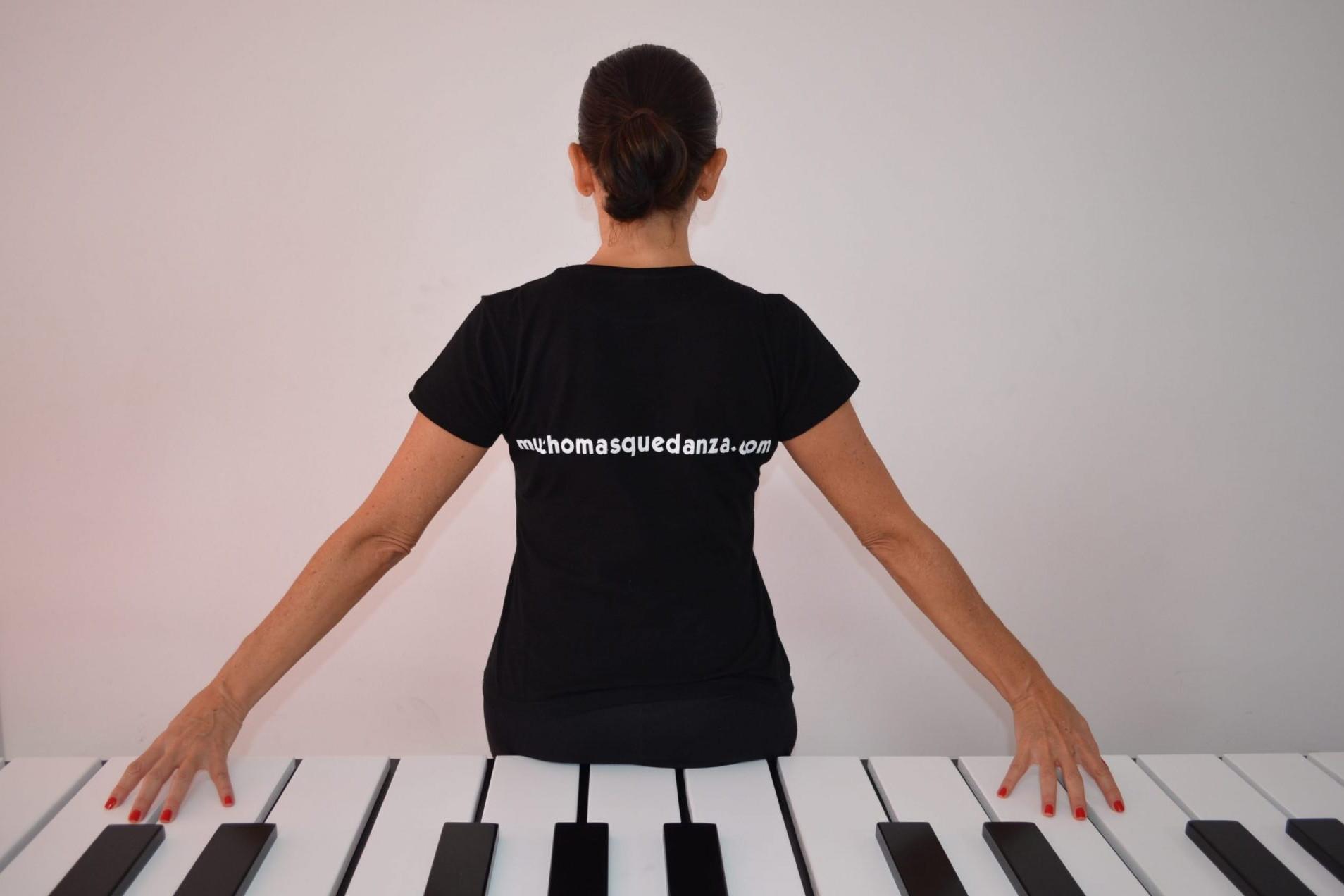 Foto de la directora del Centro de Danza Sandra Santa Cruz de espaldas sentada sobre las teclas de un piano gigantesco y en cuya camiseta se lee la filosofía del Centro: Muchomasquedanza.