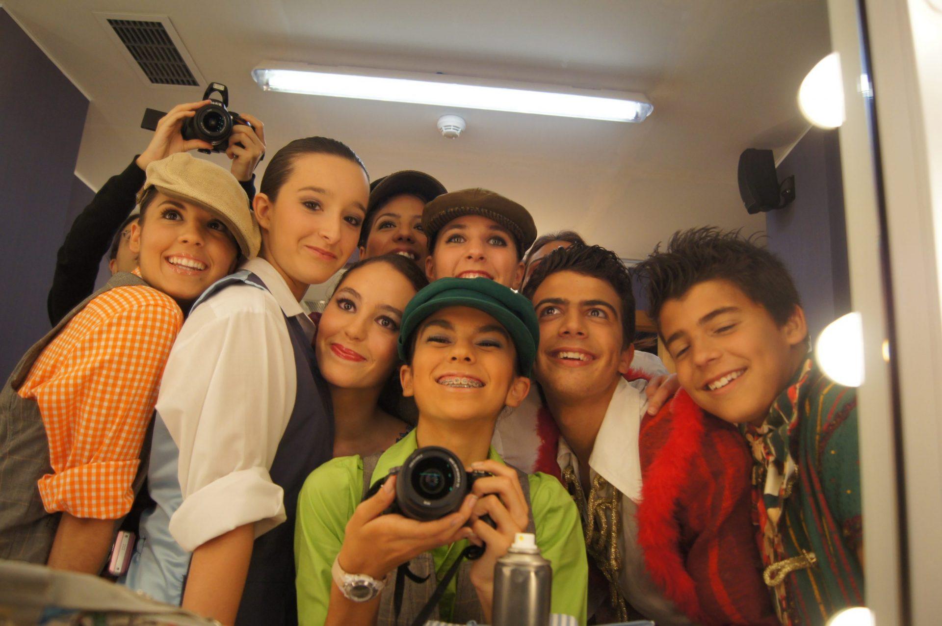 Foto del Centro de Danza Sandra Santa Cruz donde un grupo de alumno posa mirándose al espejocon una amplia sonrisa y la bailarina del centro lleva una cámara de fotos.