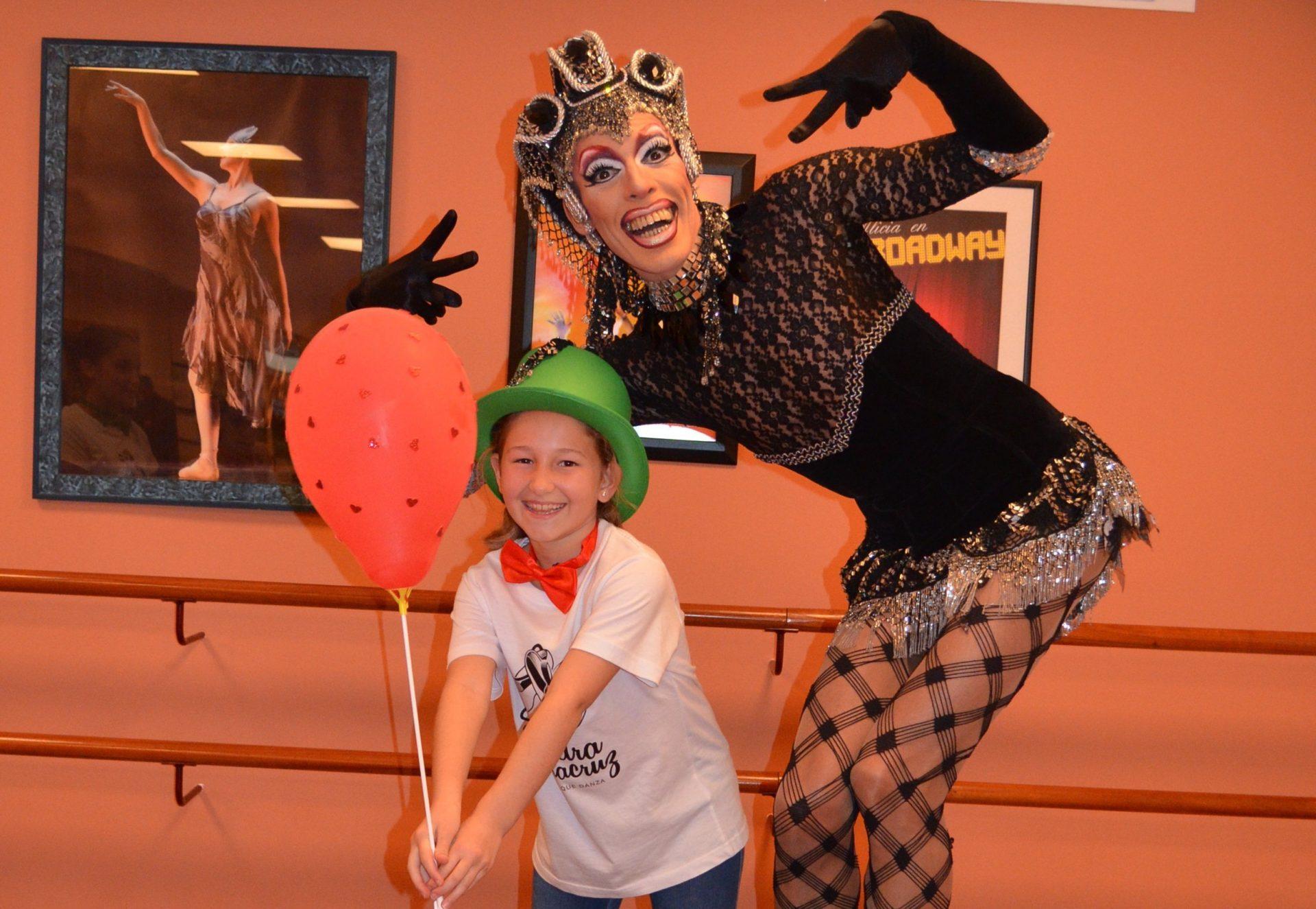 Foto de Pio Drag en el Centro de Danza Sandra Santa Cruz con una de sus alumnas que lleva puesta una pajarita roja y un bombín verde y que sujeta un globo rojo