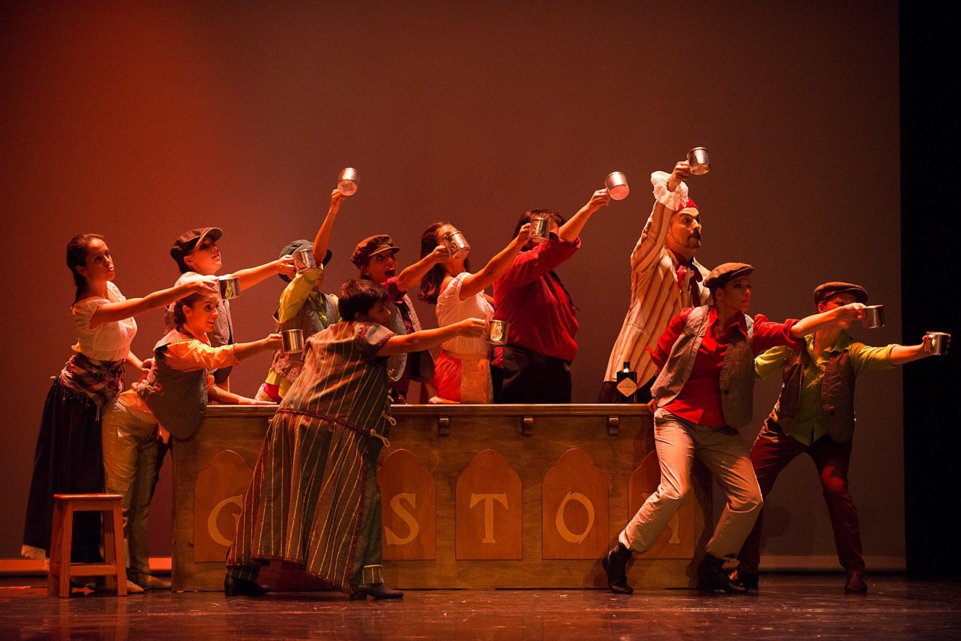 Foto del alumnado del Centro de Danza Sandra Santa Cruz von tazas en las manos alrededor de una barra de madera que dice