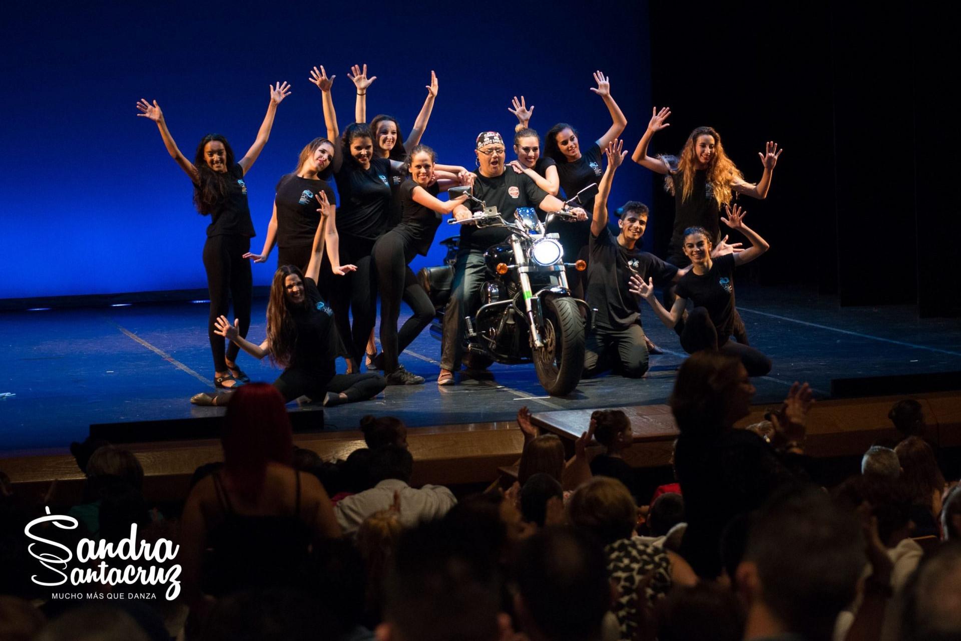 Foto de un espectáculo del Centor de Danza Sandra Santa Cruz con una motosobre le escenario y los bailarines bailan a su alrededor.