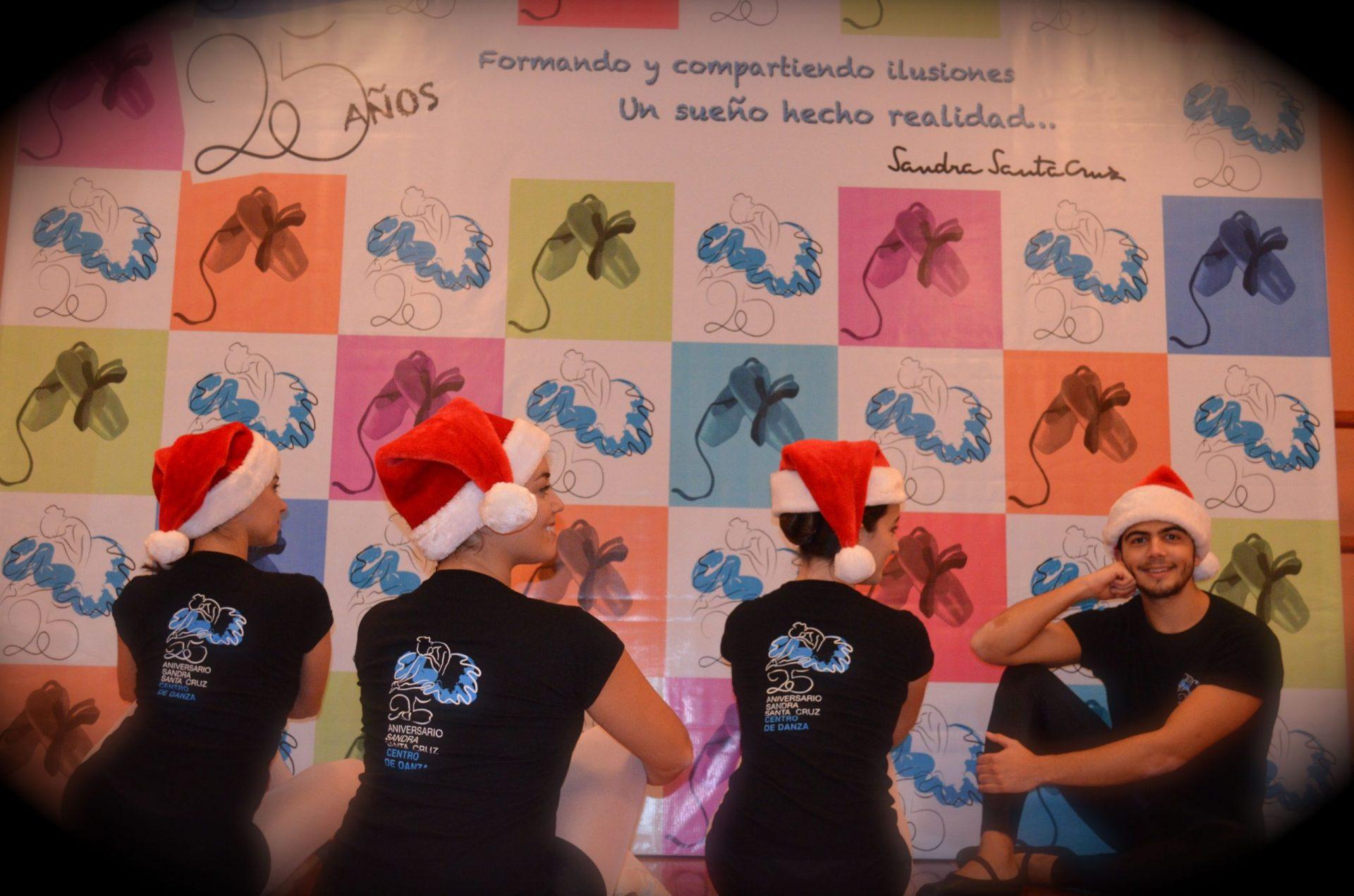 Foto de 4 bailarines del Centro de Danza Sandra Santa Cruz sentados en la sala de la escuela delante del Photocall de su 25 Aniversario y con su gorrito de Papa Noel en la cabeza y una copa de campán en la mano, para felicitar a todos.