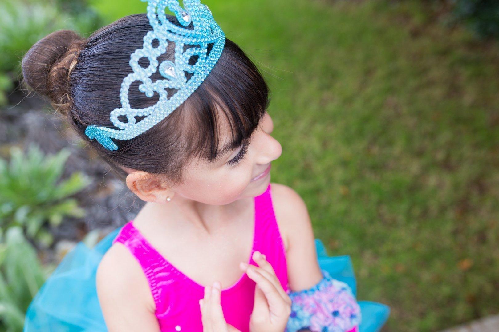 Foto en el campo de una alumna de 6 años Centro de Danza Sandra Santa Cruz vestida con tutú fucsia y malva y una diadema de princesa con las manos haciendo