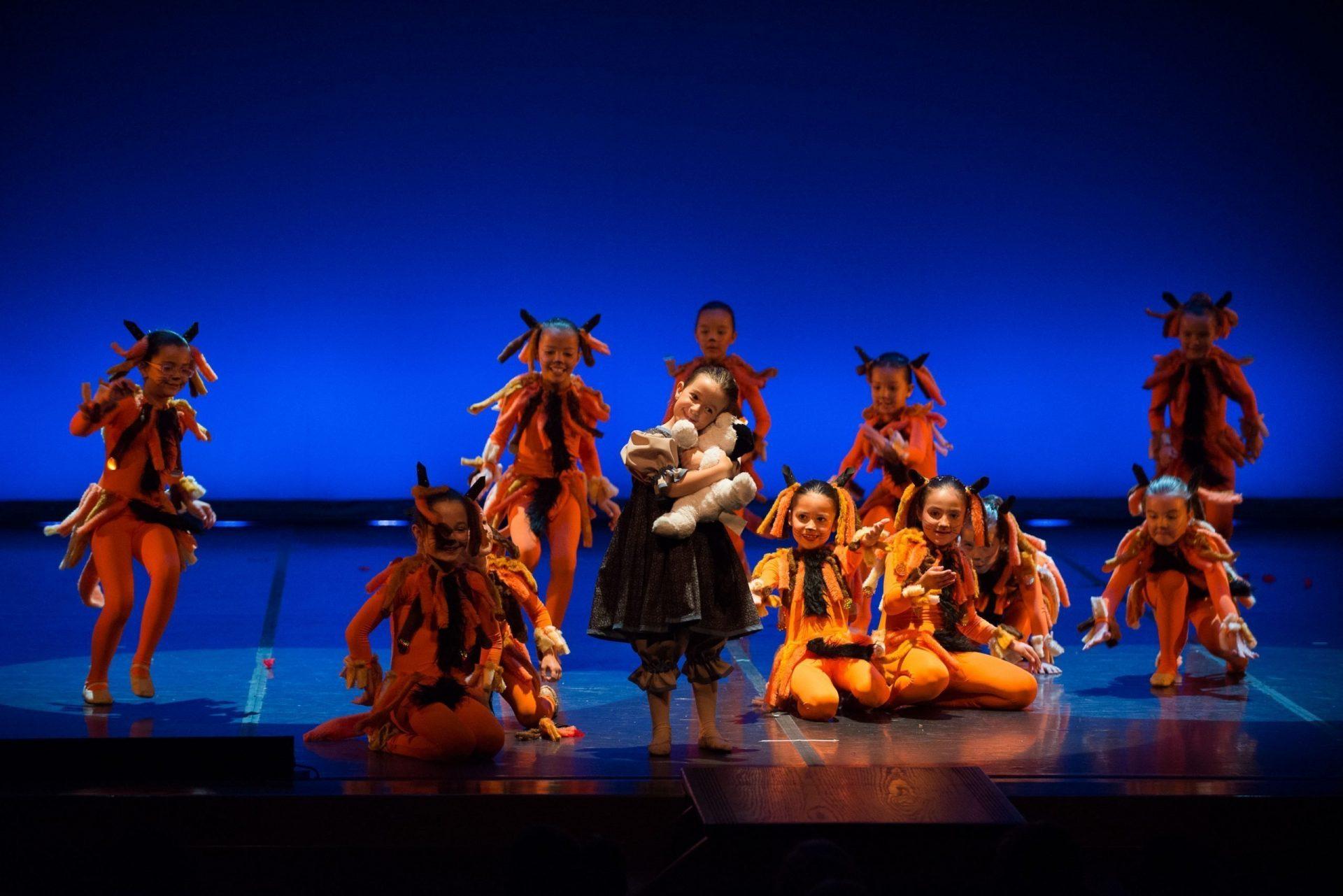 Foto de un grupo de bailarianas del Centro de Danza Sandra Santa Cruz de 6 años, vestidas de gatos y en el centro de la foto una niña con un gatito cogido en sus manos