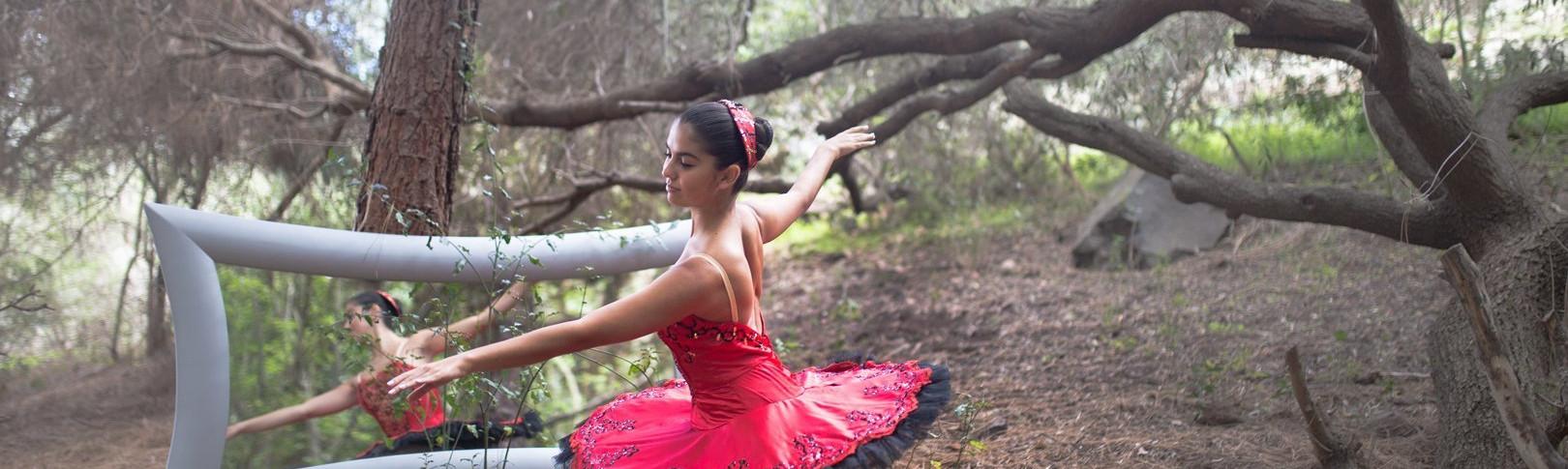 Foto de Olga Ortega, bailarina del Centro de Danza Sandra Santa Cruz en el campo vestida con un maravilloso tutú rojo de rodillas en 4ª posición y apoyada en una de sus zaaptillas de puntas con los brazos en 4ª alonyé, posando delante de un gran espejo espejo plateado de situeta con forma sinuosa